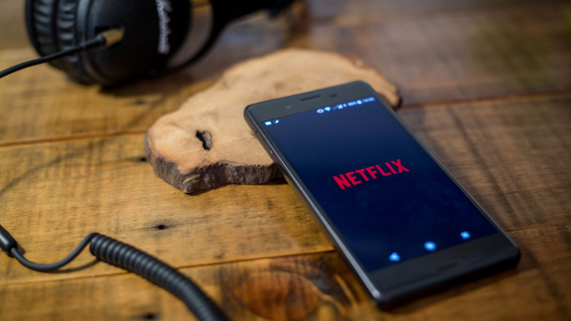 The netflix logo is displayed on a mobile phone with headphones plugged in