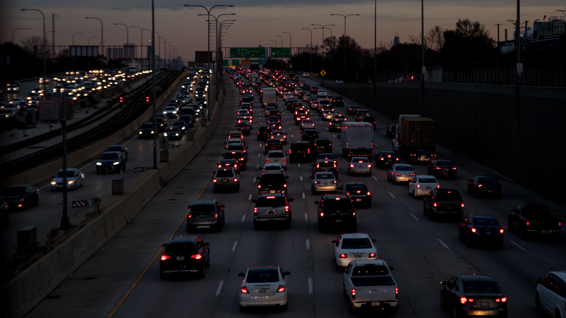 Masses of vehicles move slowly on the Montrose Ave overpass in Chicago at dusk