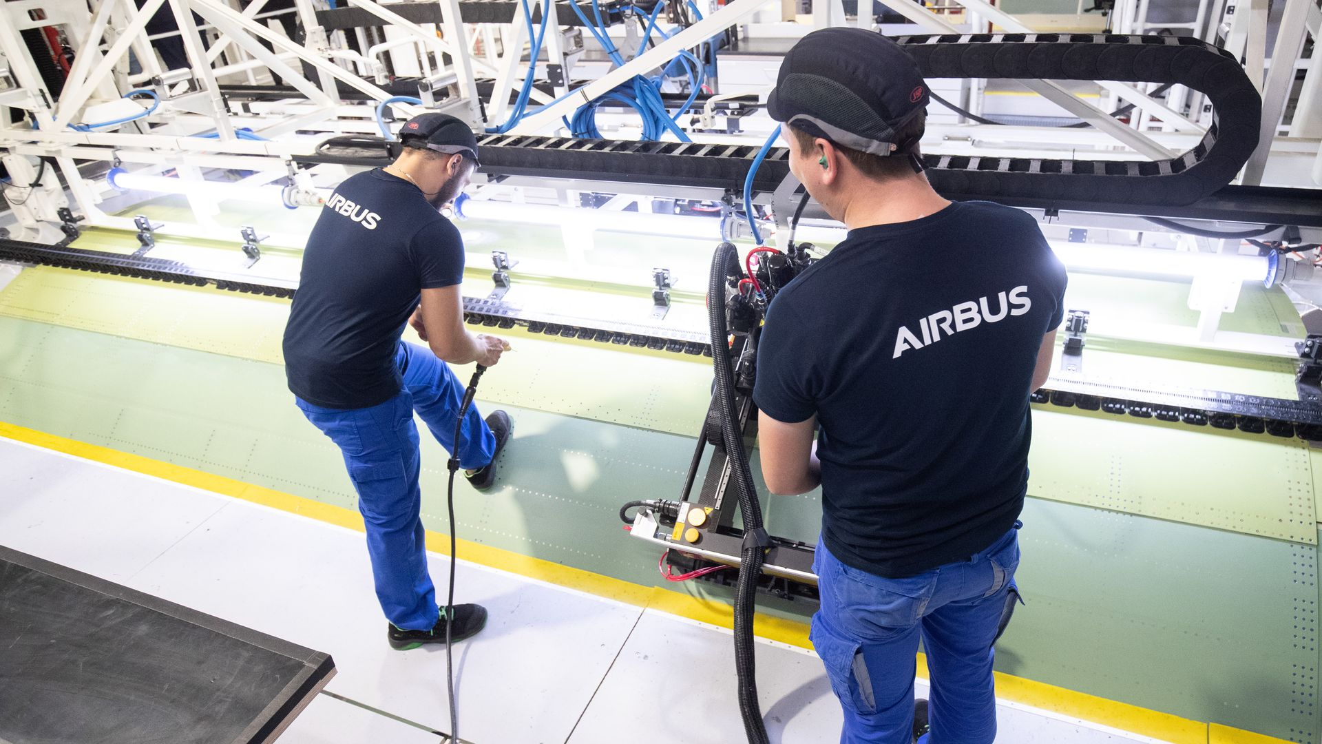 In this image, two men wearing shirts with the Airbus logo work on assembling an Airbus plane