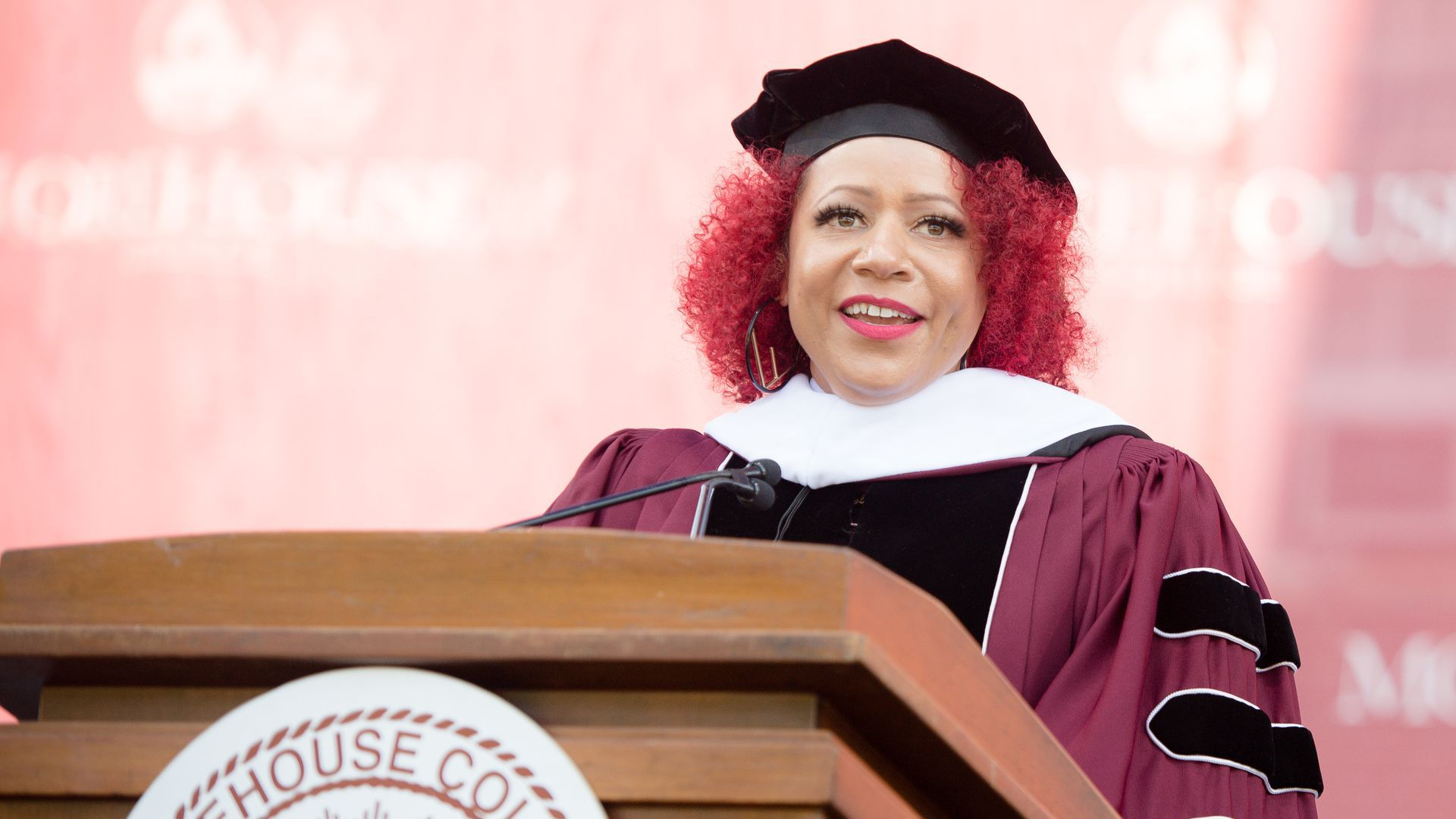 Journalist Nikole Hannah-Jones wears a cap and gown and speaks at a podium