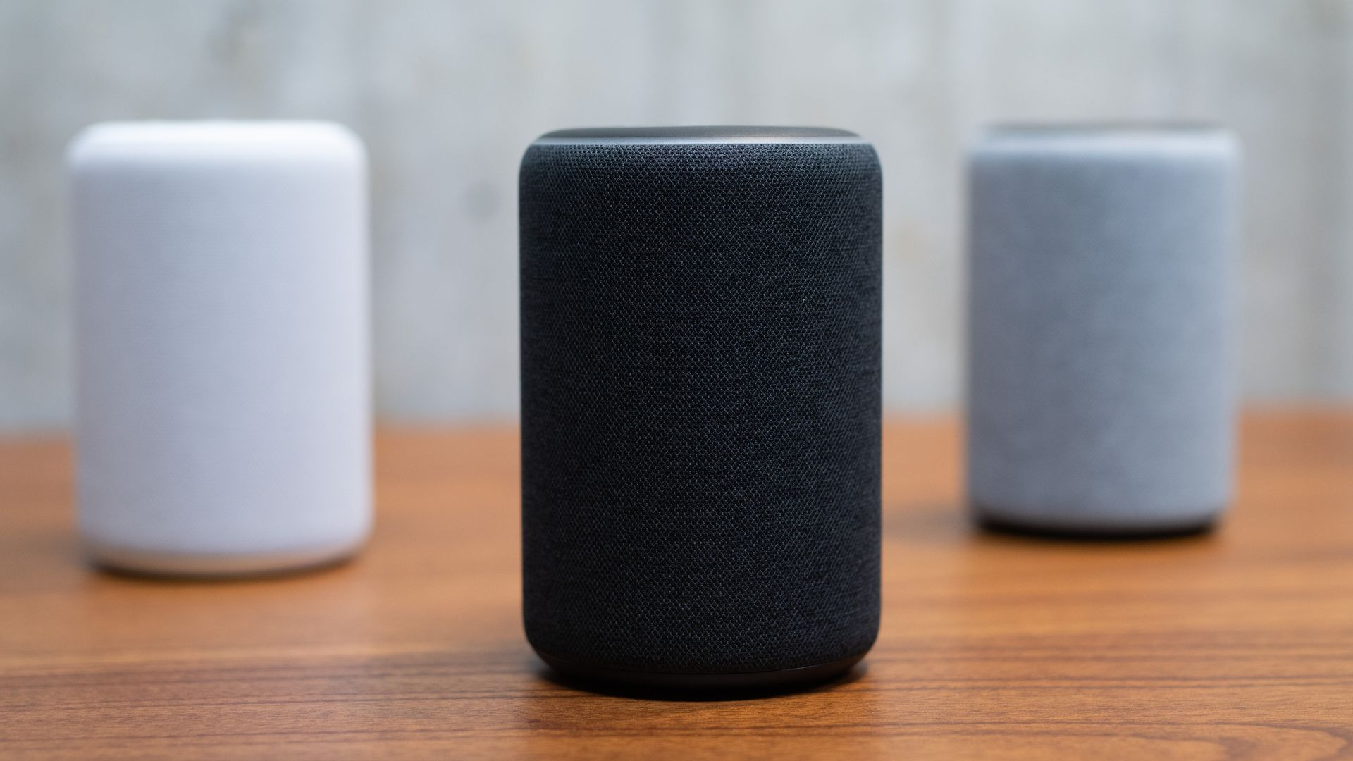 In this image, a white Amazon Alexa sits next to a black one and a gray one on a wooden countertop.