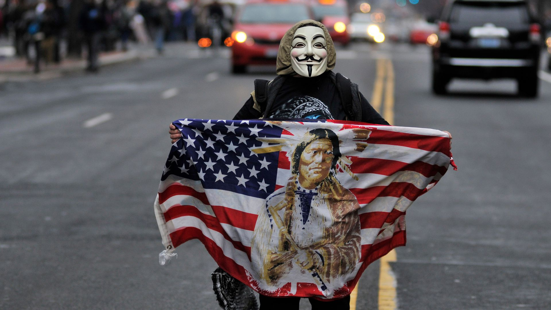 A masked person stands in the street after Trump's inauguration.