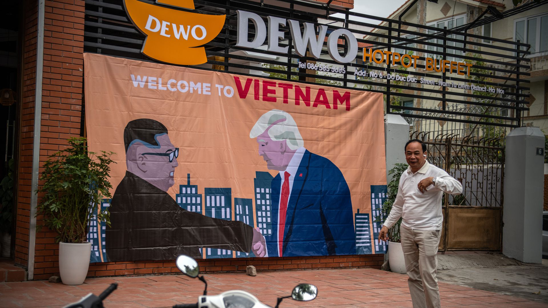 A banner showing President Donald Trump and North Korean leader Kim Jong-un shaking hands next to the words 'Welcome to Vietnam'