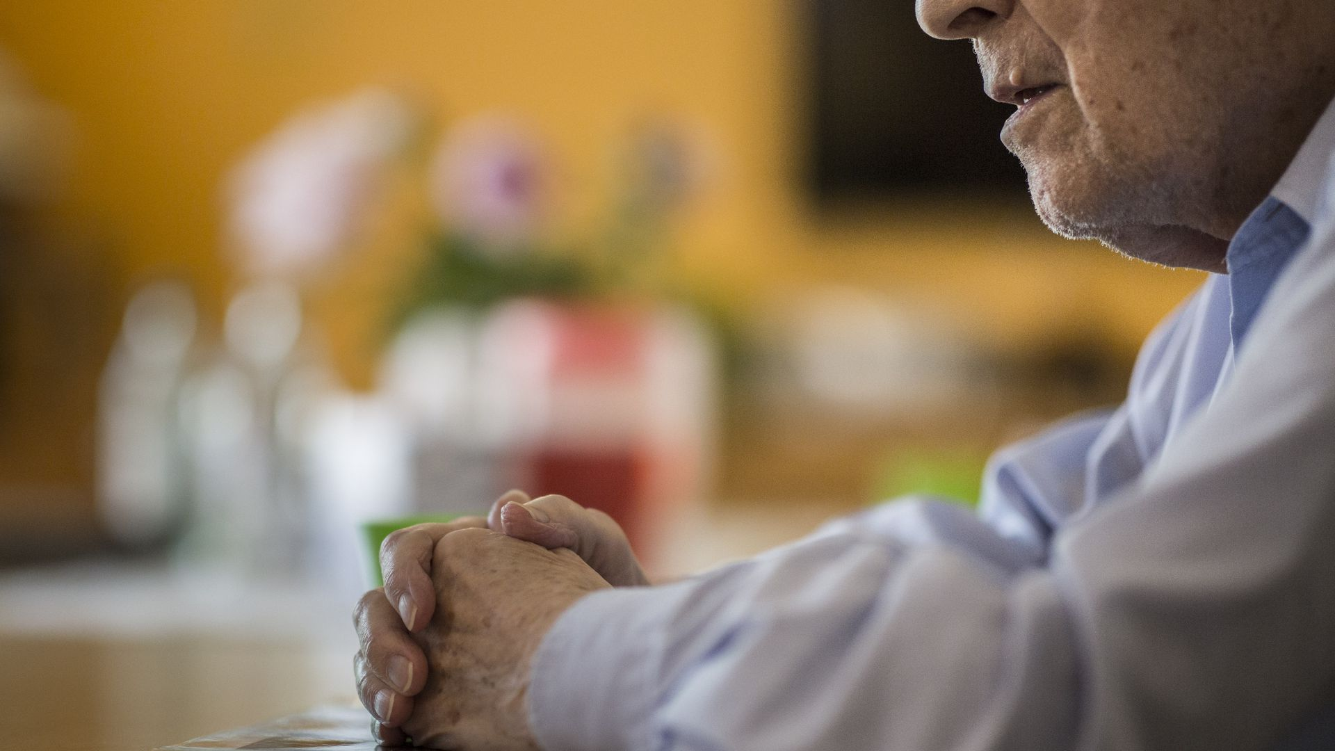 An elderly man sits at a table with his hands folded.
