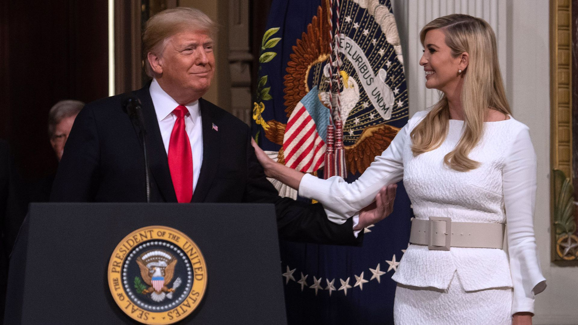 In this image, Ivanka stands next to Trump as he stands behind a podium. She smiles at him and places a hand on his shoulder.