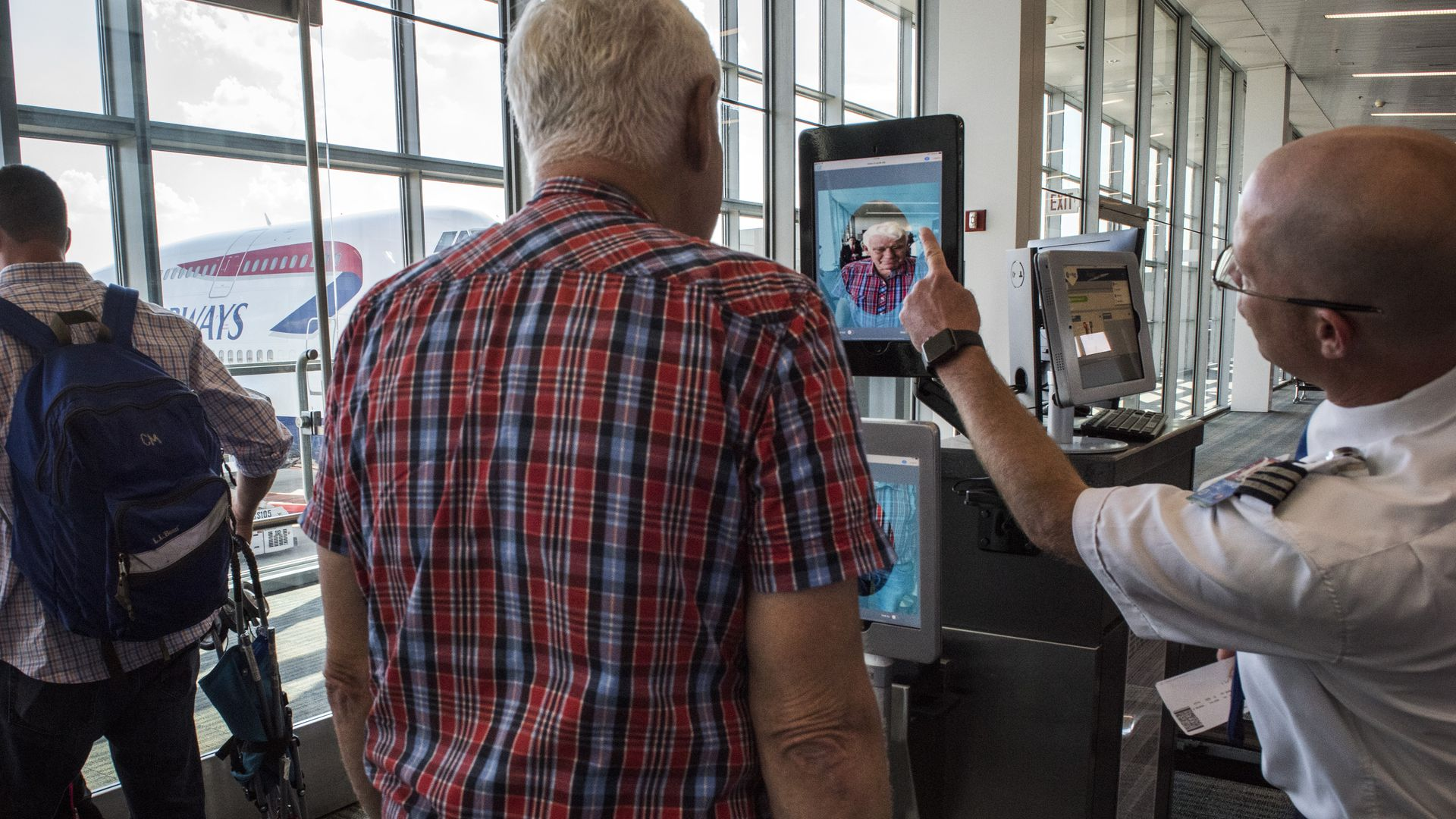 A man looks into a tablet showing his own face as another man points to it