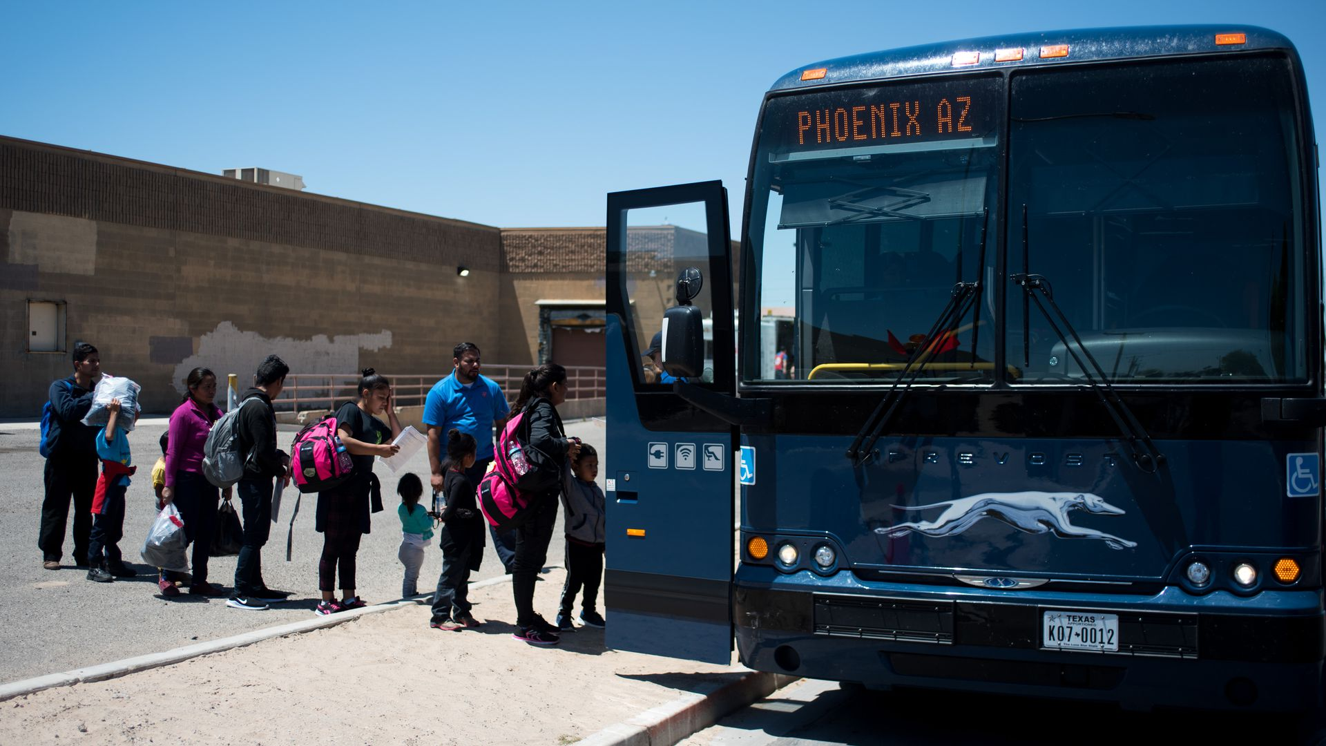 This image shows a line of children boarding a bus.