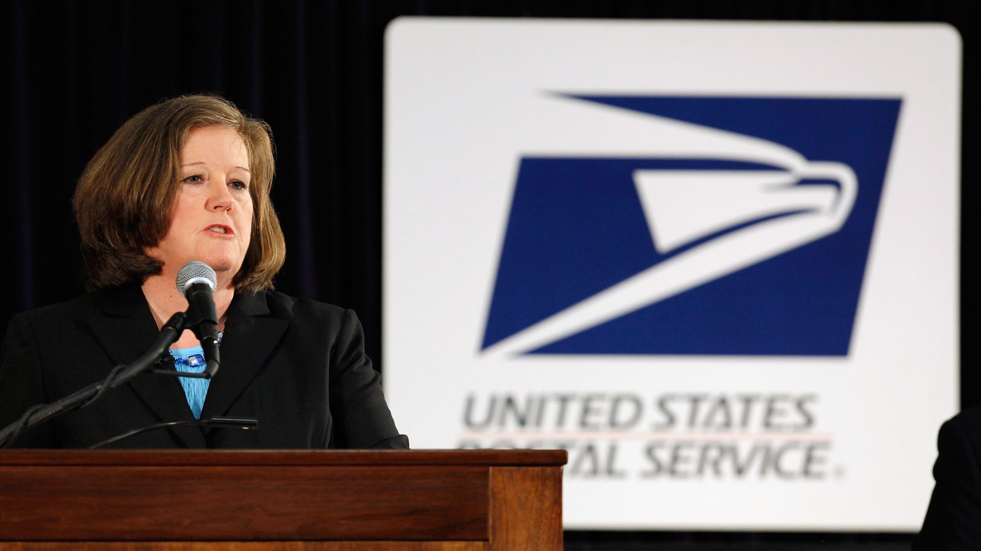 In this image, Brennan speaks from behind a podium while the U.S. Postal Service logo stands behind her.