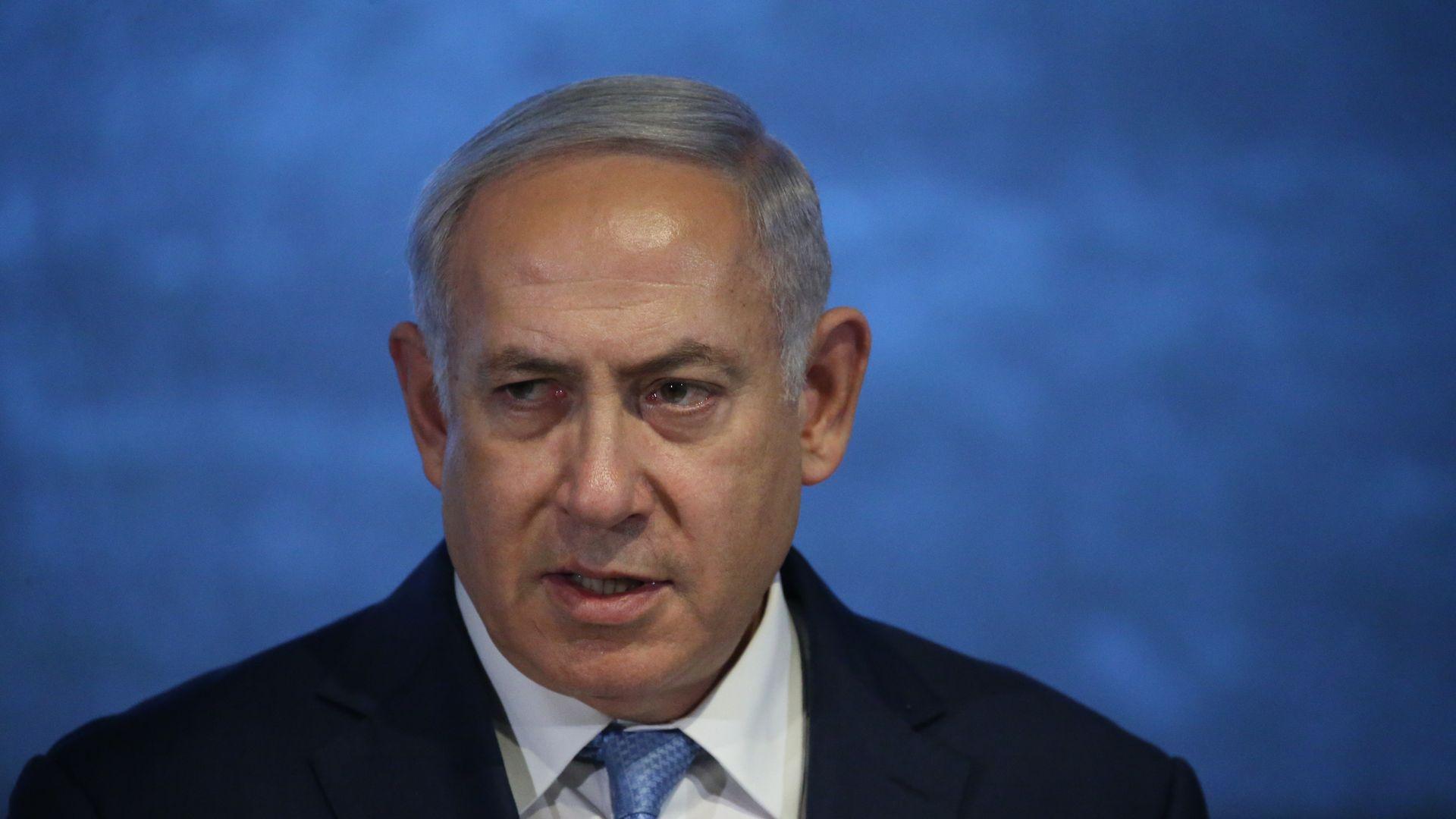 Benjamin Netanyahu before a blue backdrop.