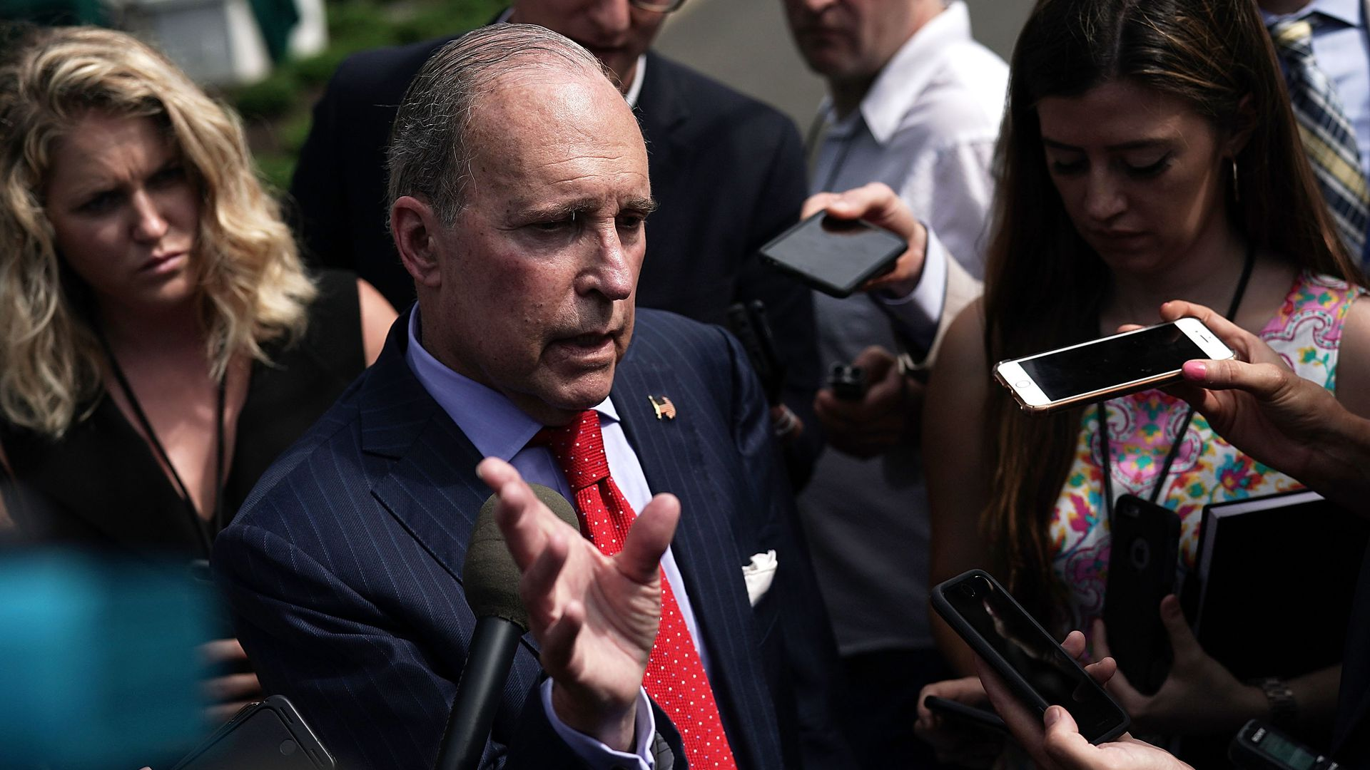 Larry Kudlow in the middle of a crowd of reporters