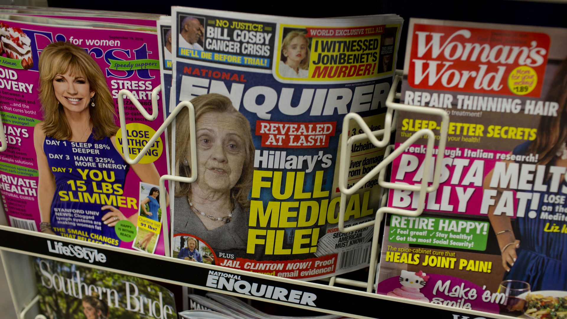 In this image, a stack of National Enquirer magazines sit between two others in a store rack.