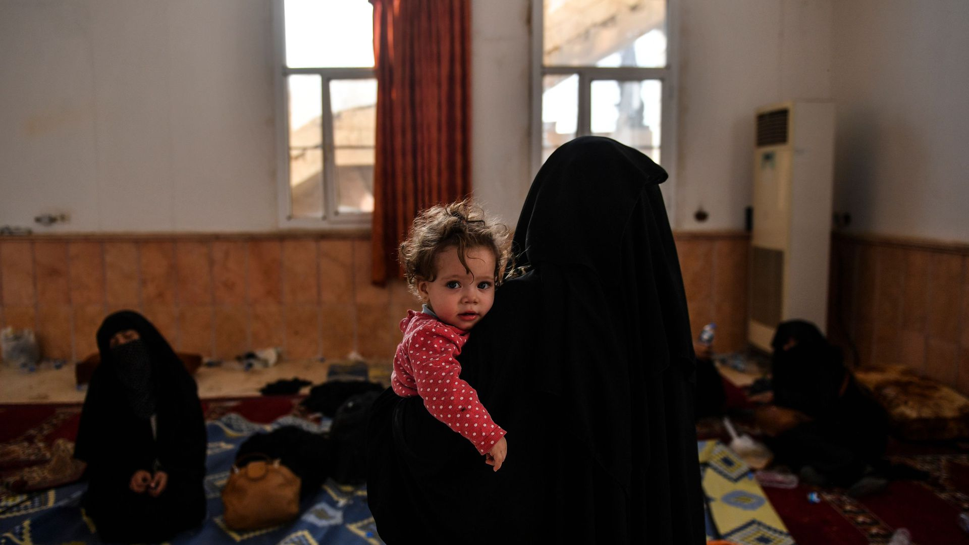 A woman holds a child in an open room.