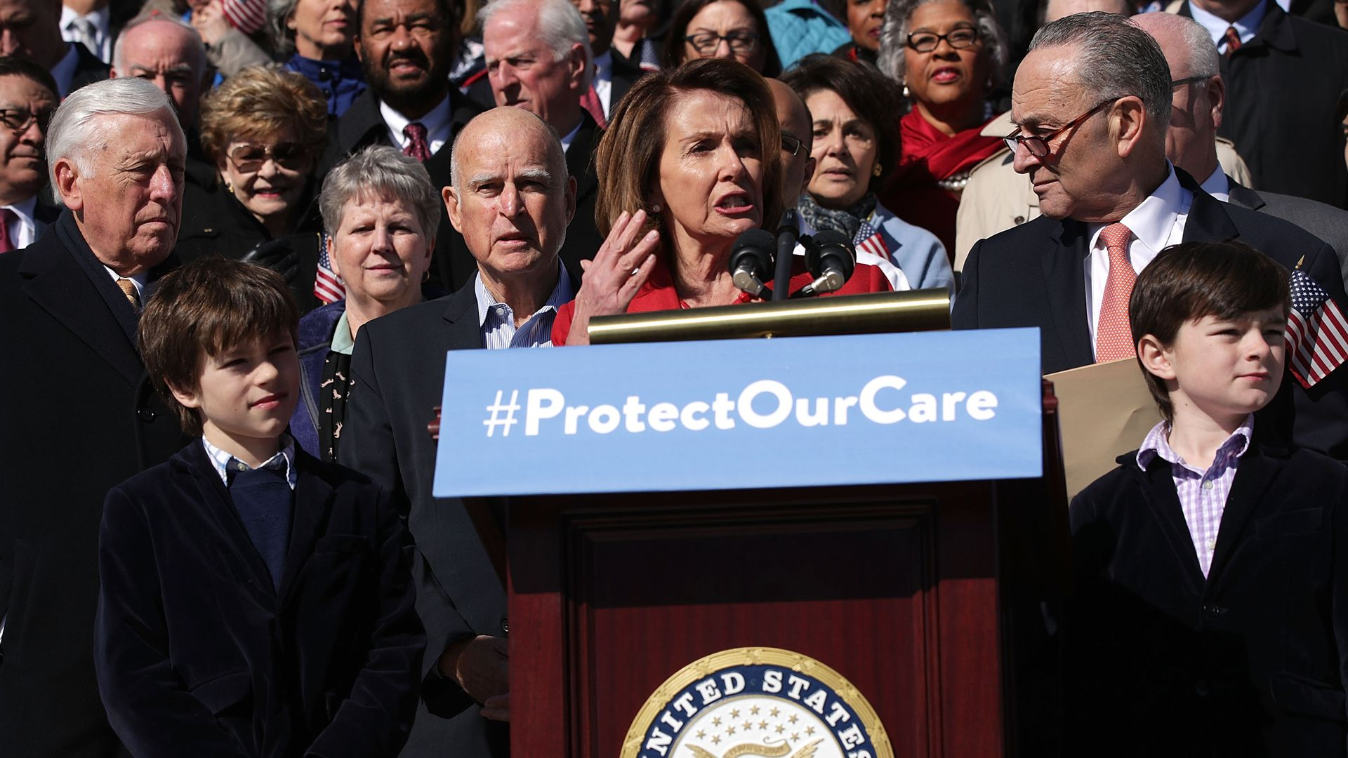 "In this image, Nancy Pelosi stands outside with a crowd of lawmakers behind her, at a podium with a sign that reads ""#ProtectOurCare."""