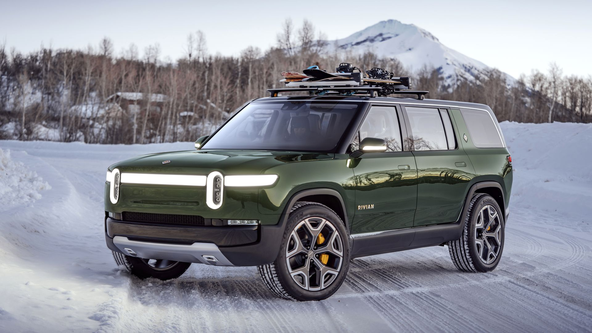 Image of green Rivian R2S sport utility in a snowy environment.