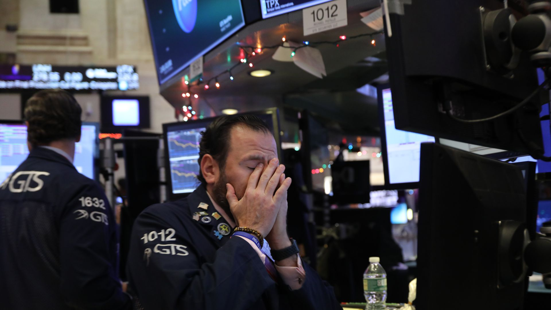 Stock trader with hands over his face.