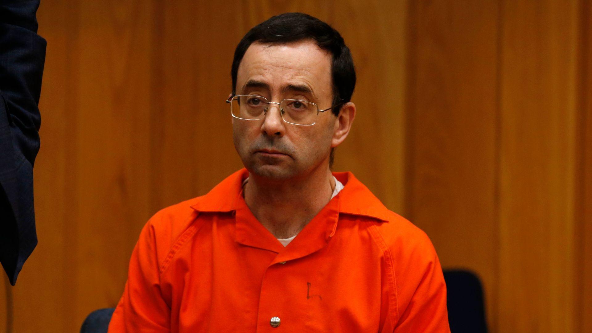 Larry Nassar in orange jumpsuit looks sad.