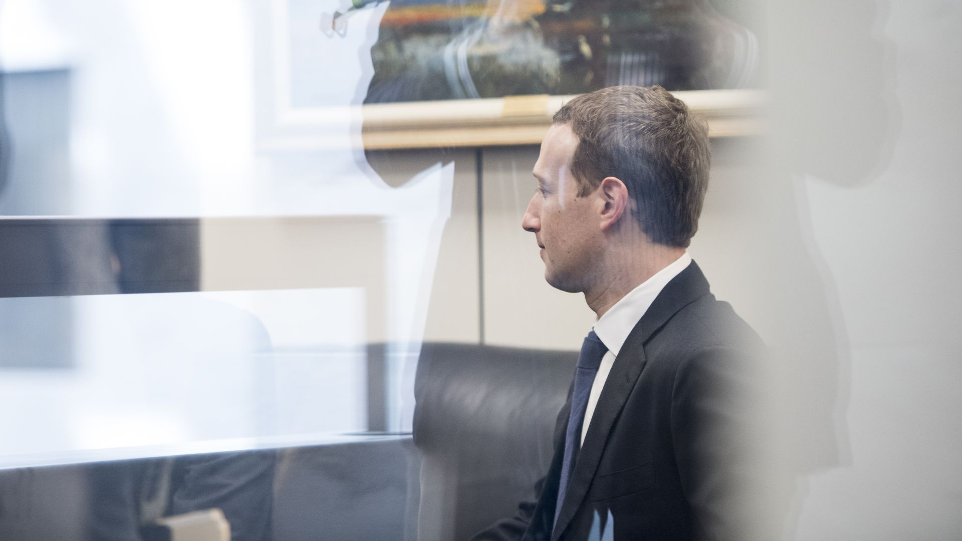 Facebook CEO Mark Zuckerberg seated, looking away, photographed through a window