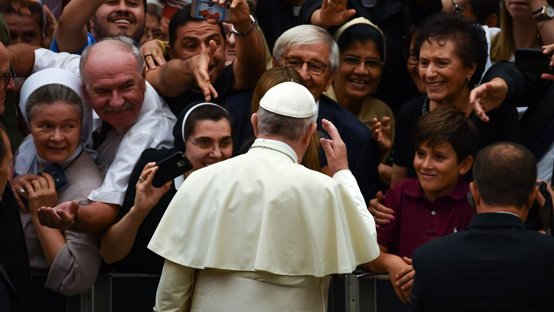 Pope Francis standing in front of a crowd.