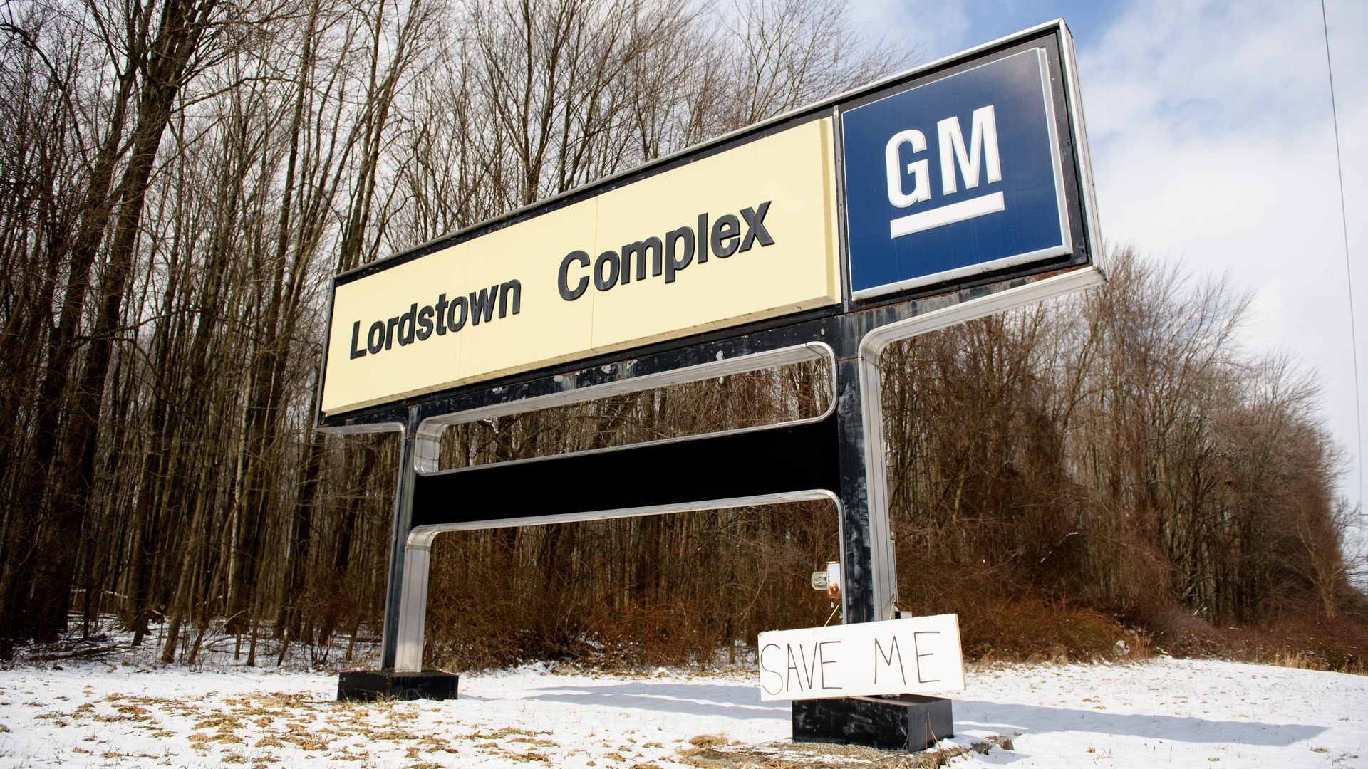 """In this image, handmade sign reading """"save me"""" leans against a large General Motors sign for the closed Lordstown Complex."""