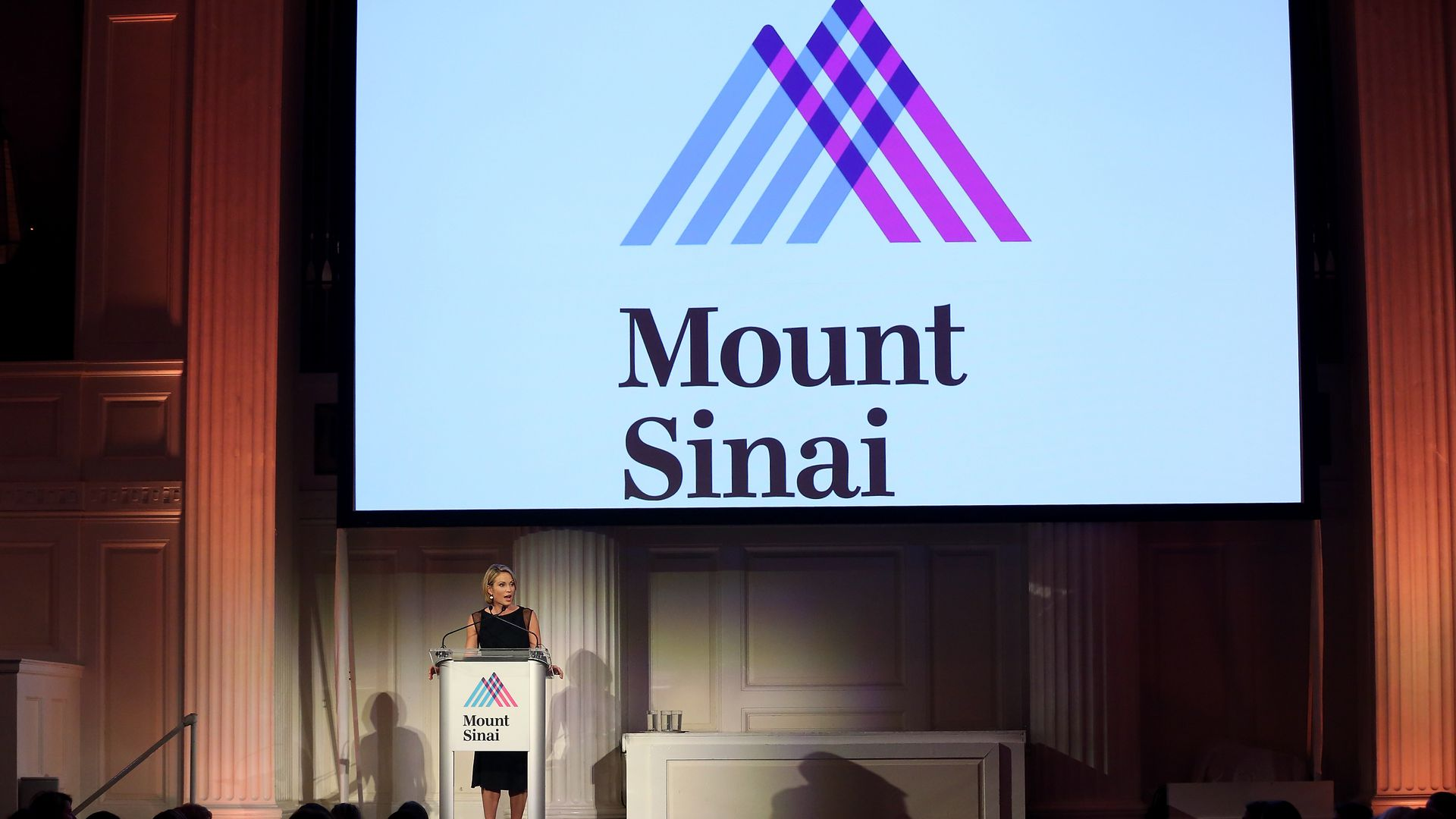 A woman speaks near a large white screen that displays the blue and pink logo for Mount Sinai Health System.