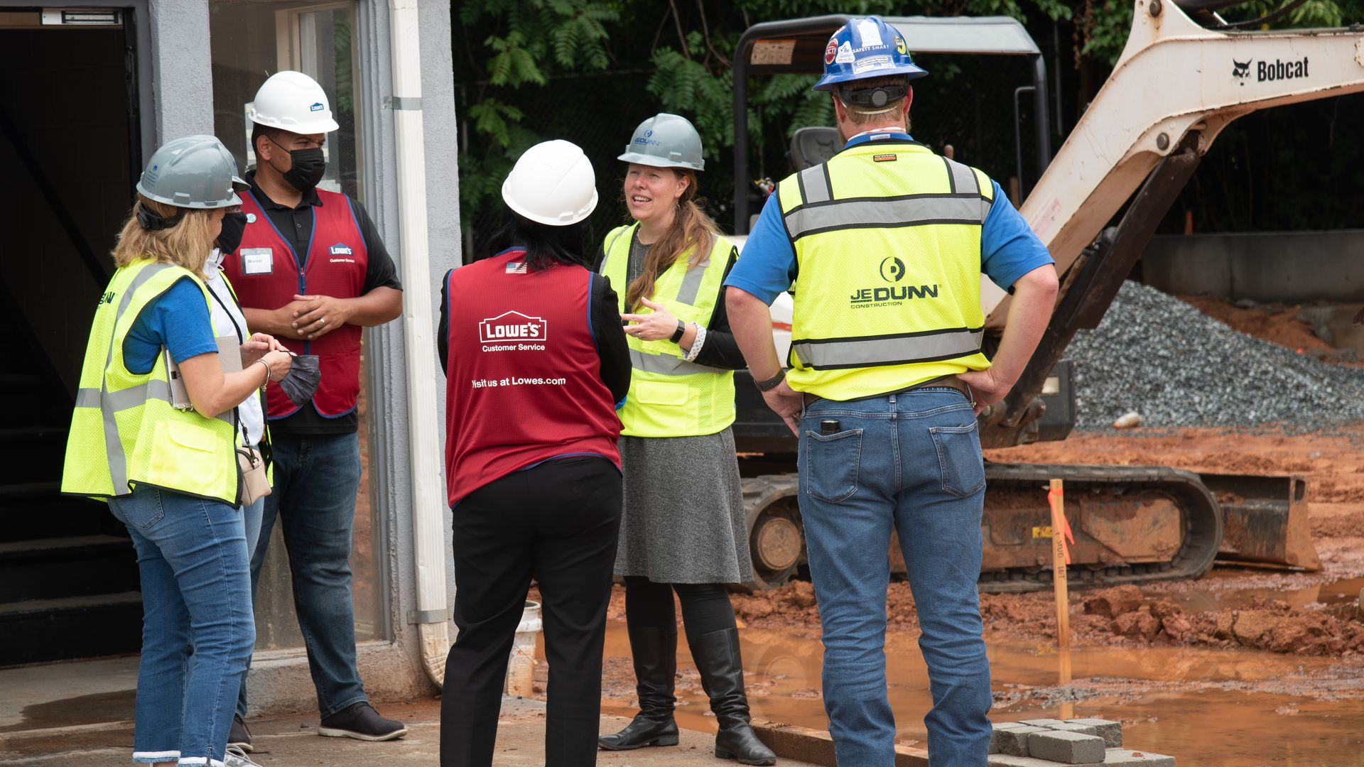 Five people standing and conversing in a circle at a construction site. They're all wearing hard hats and reflective vests.