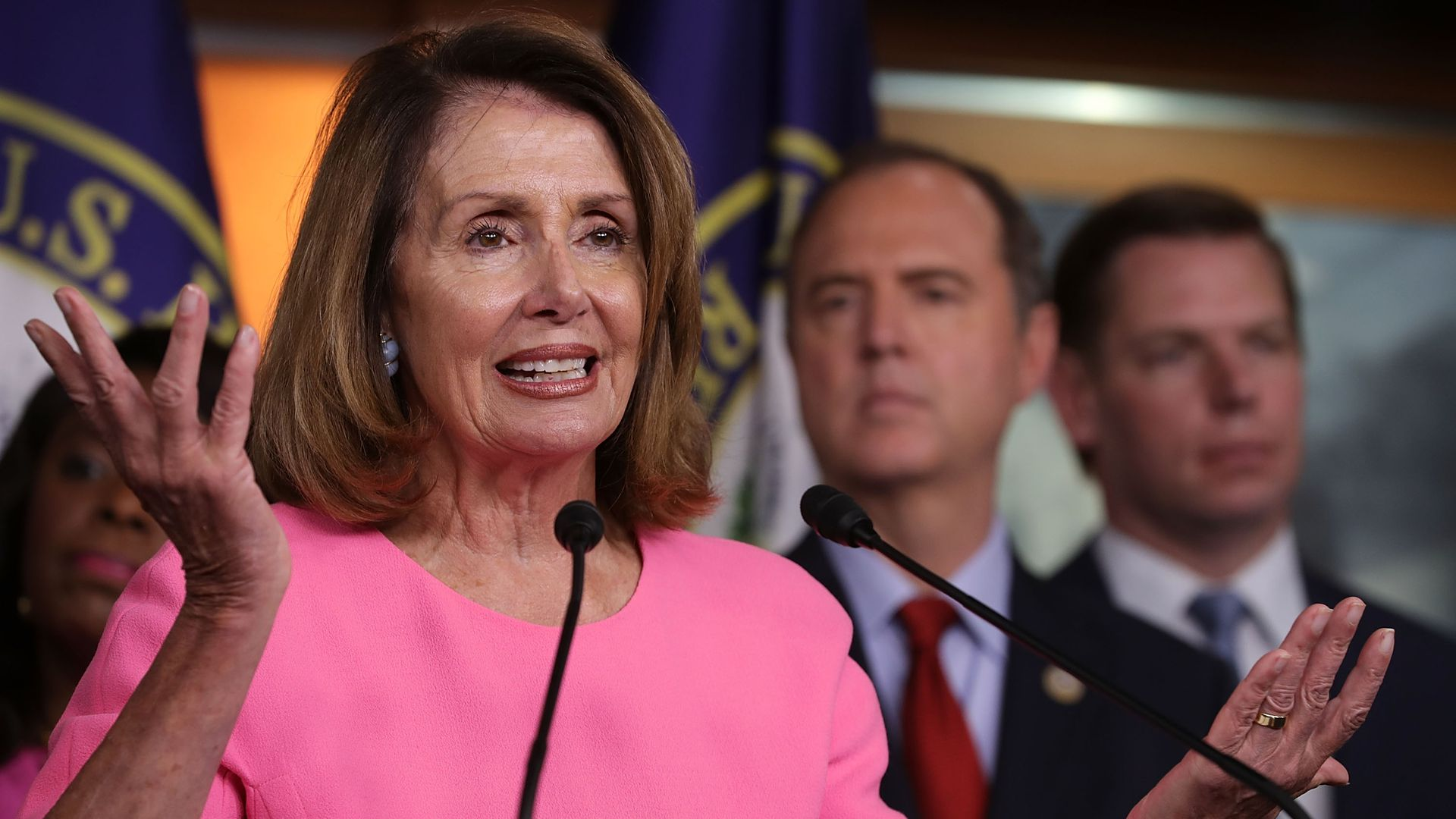 Nancy Pelosi in pink standing in front of Democrats raises her arms in a shrug smiling.