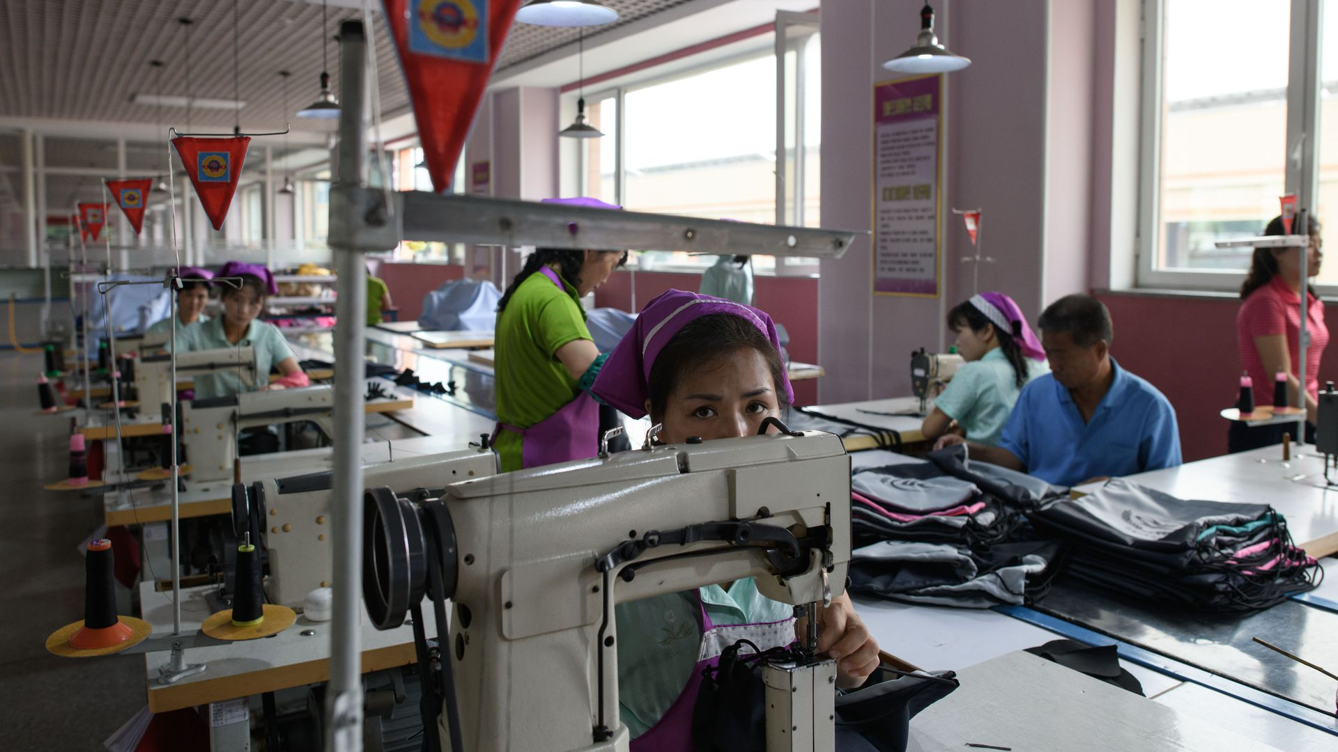 A North Korean woman with a pink bandana looks at the camera over a sewing machine in a factory
