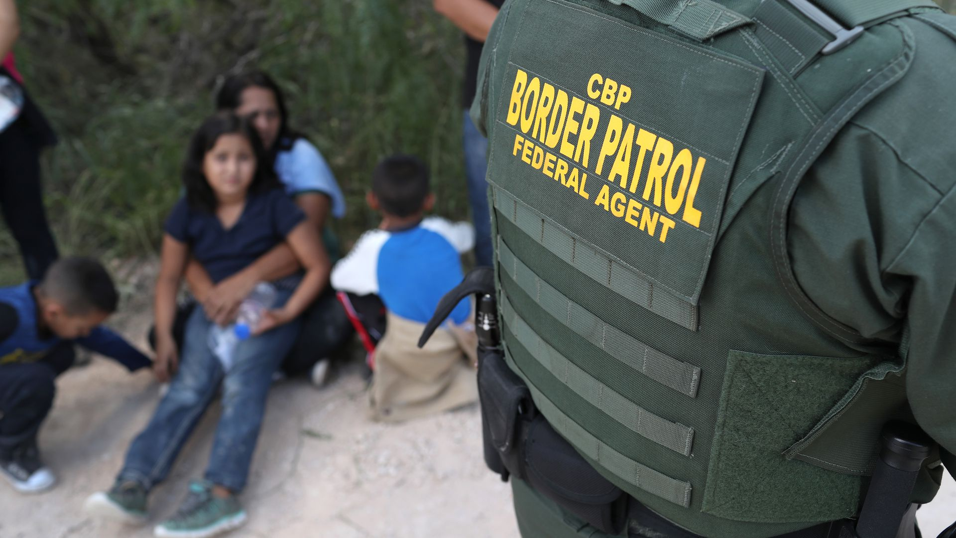 Border Patrol agent jacket with arrested immigrants sitting in the sand in the background