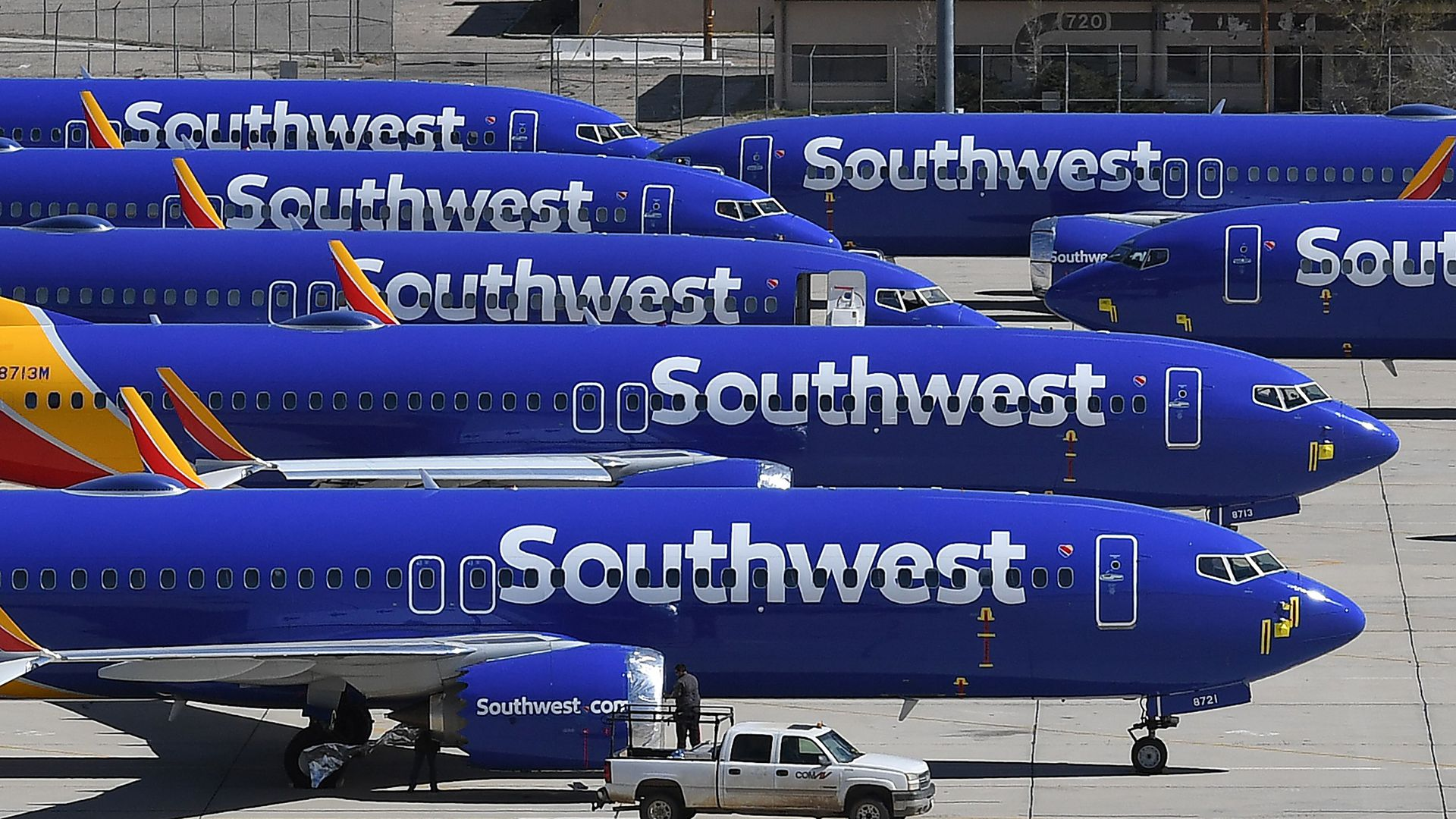 Several blue Southwest Airlines jets are parked on a tarmac.