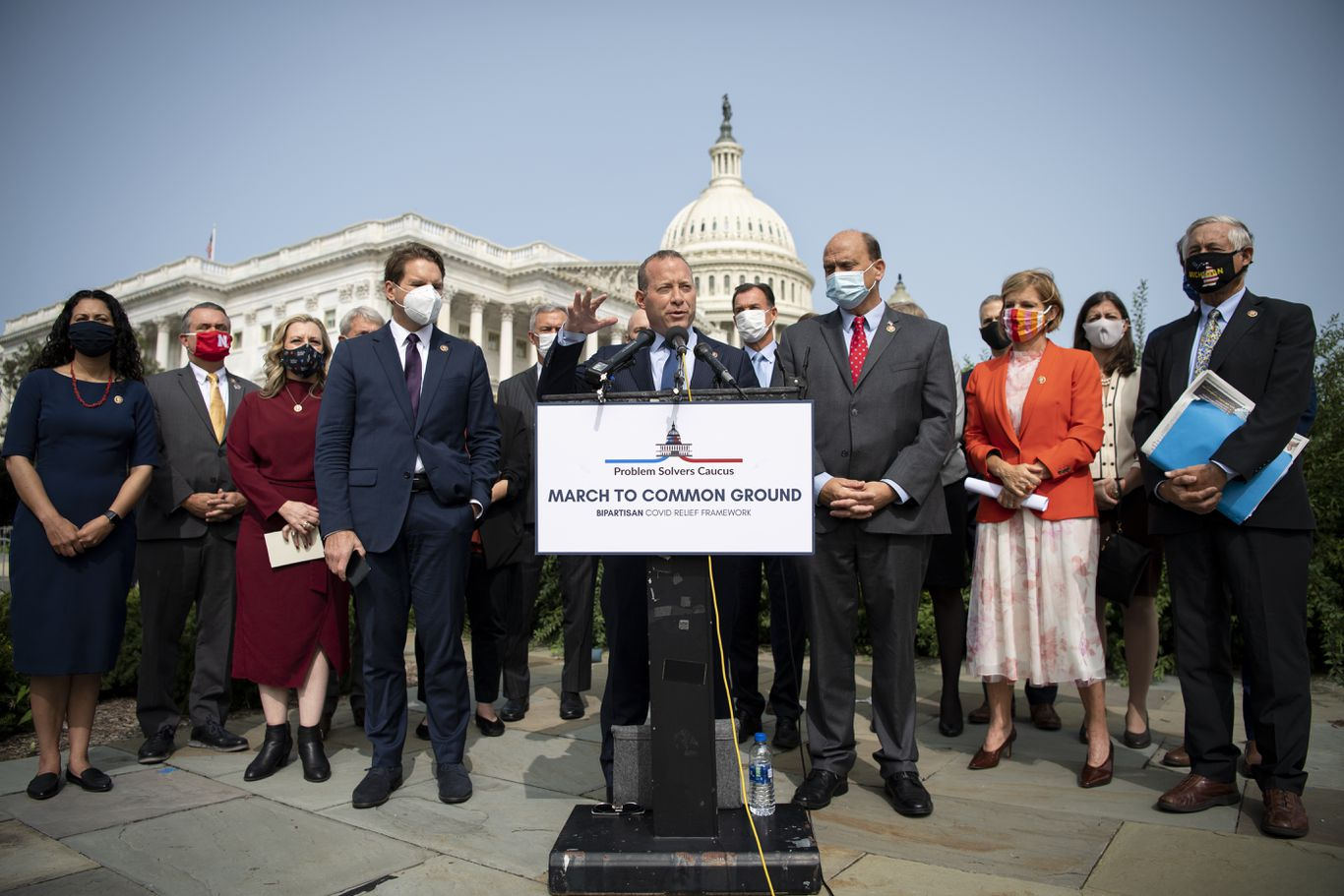 people speaking at an outdoor press conference in front of U.S. capitol