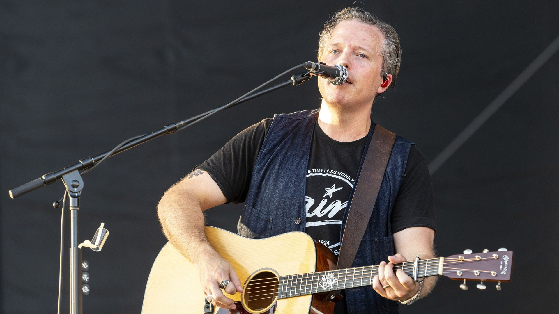 Jason Isbell singing and playing guitar at an event in August.