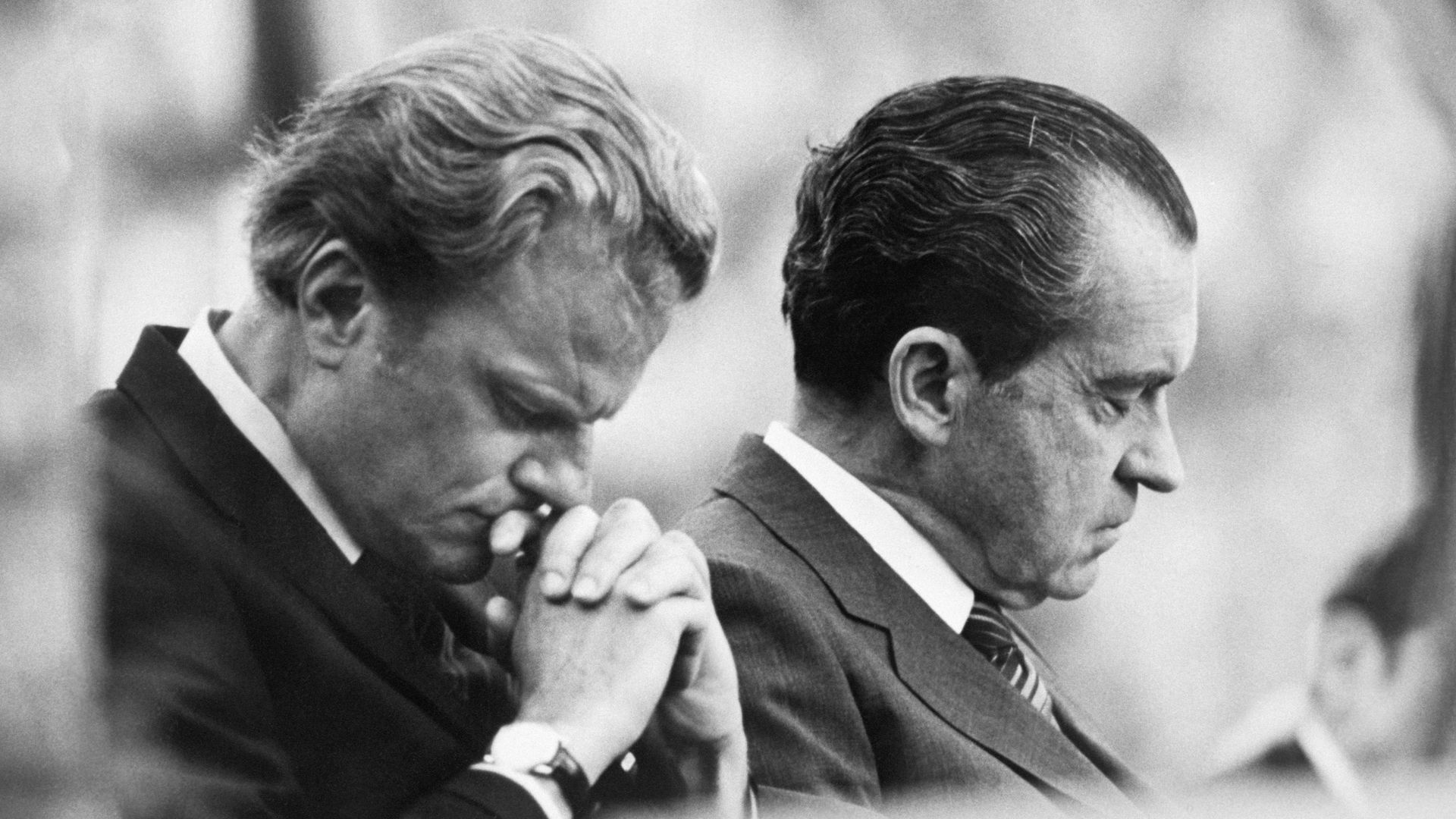 Graham and Nixon bow their heads in prayer