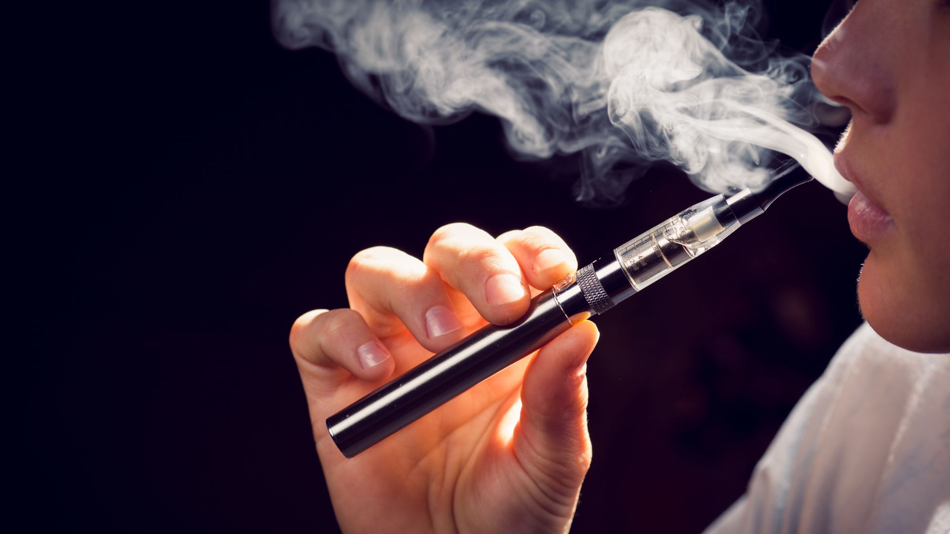 In this image, a young person holds an e-cigarette and vapes.