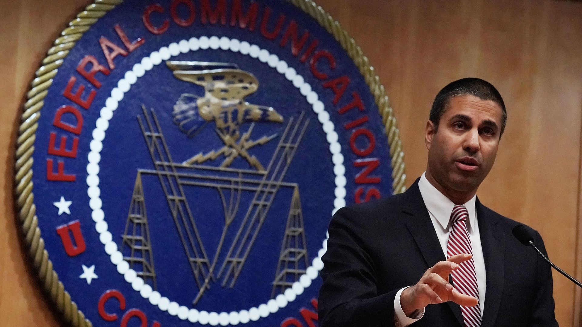 A photo of FCC Chairman Ajit Pai standing and speaking in front of the FCC logo.