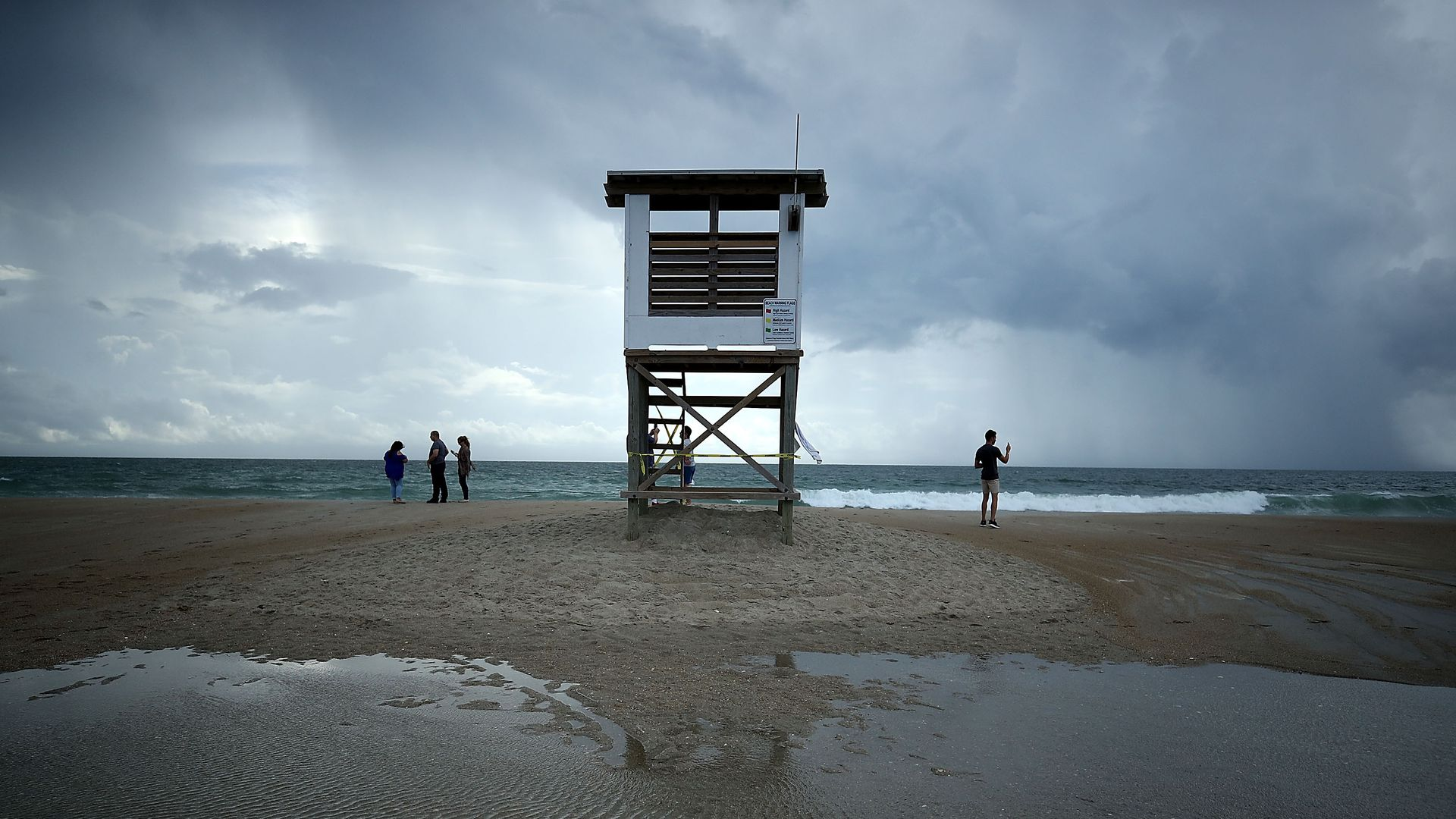 People stand near a lifeguard stand as Hurricane Florence approaches, on September 11, 2018 in Wrightsville Beach, North Carolina.