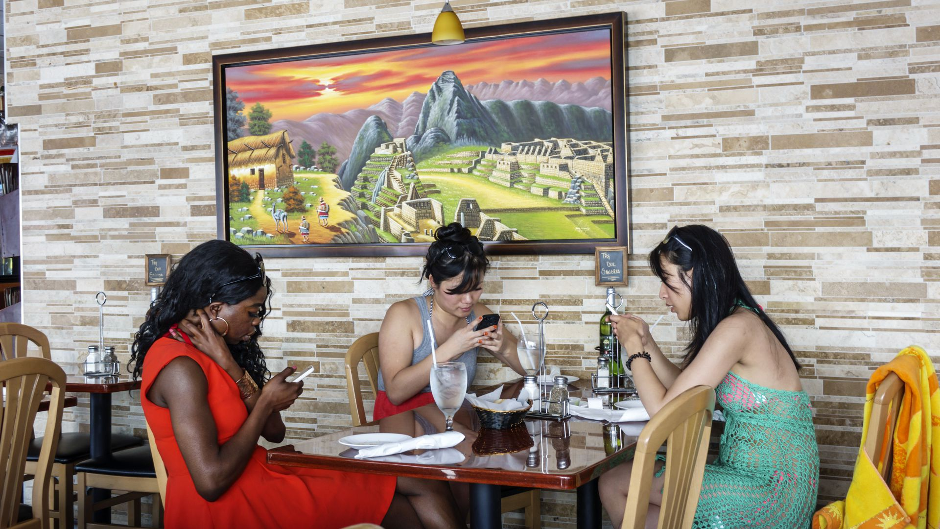 Three women sit around a restaurant table looking at their smart phones.