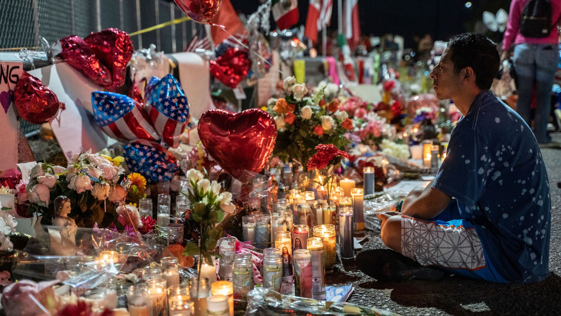 A man sitting at a memorial for El Paso victims.