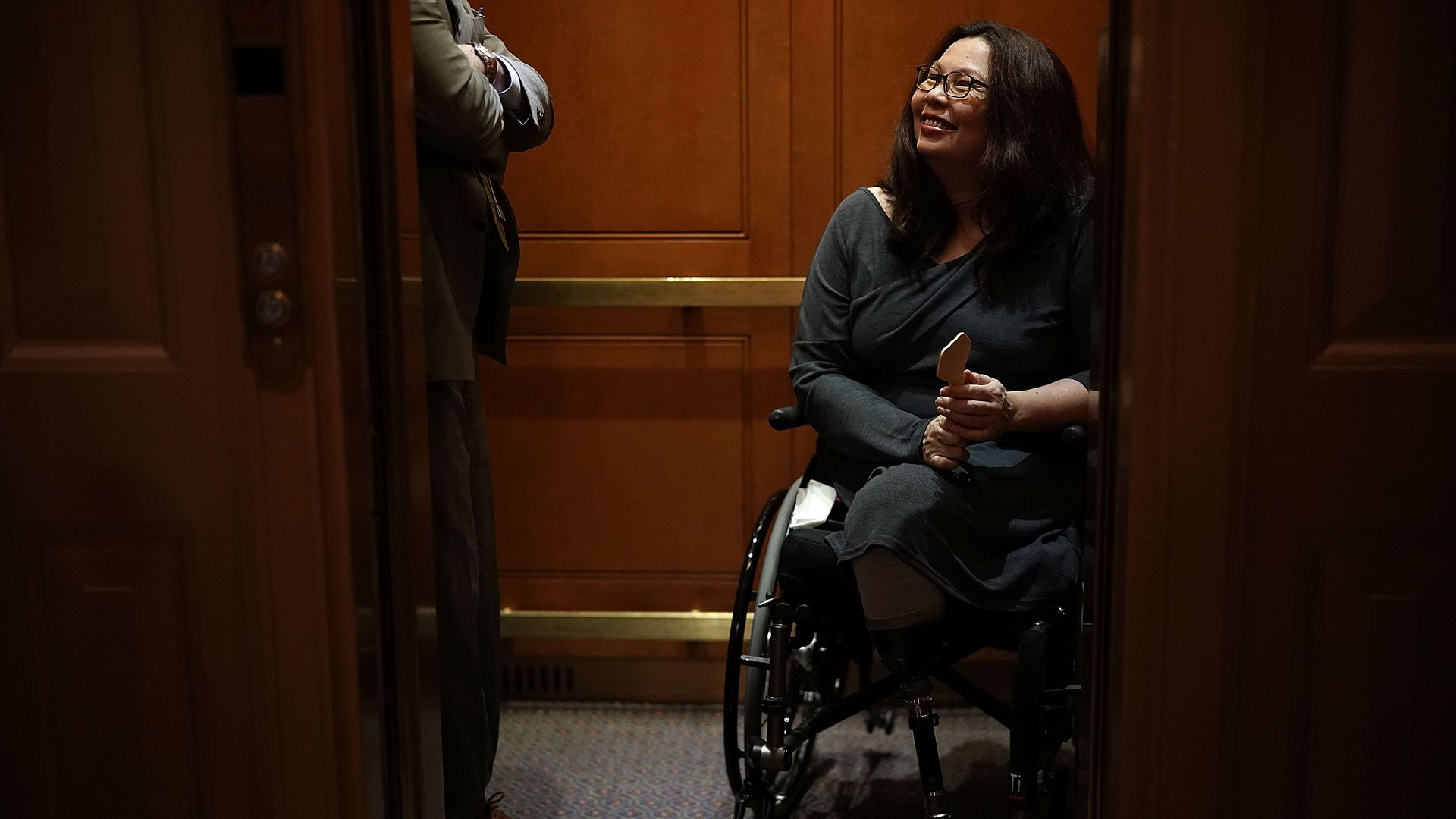 Tammy Duckworth smiles up from her wheelchair while in an elevator