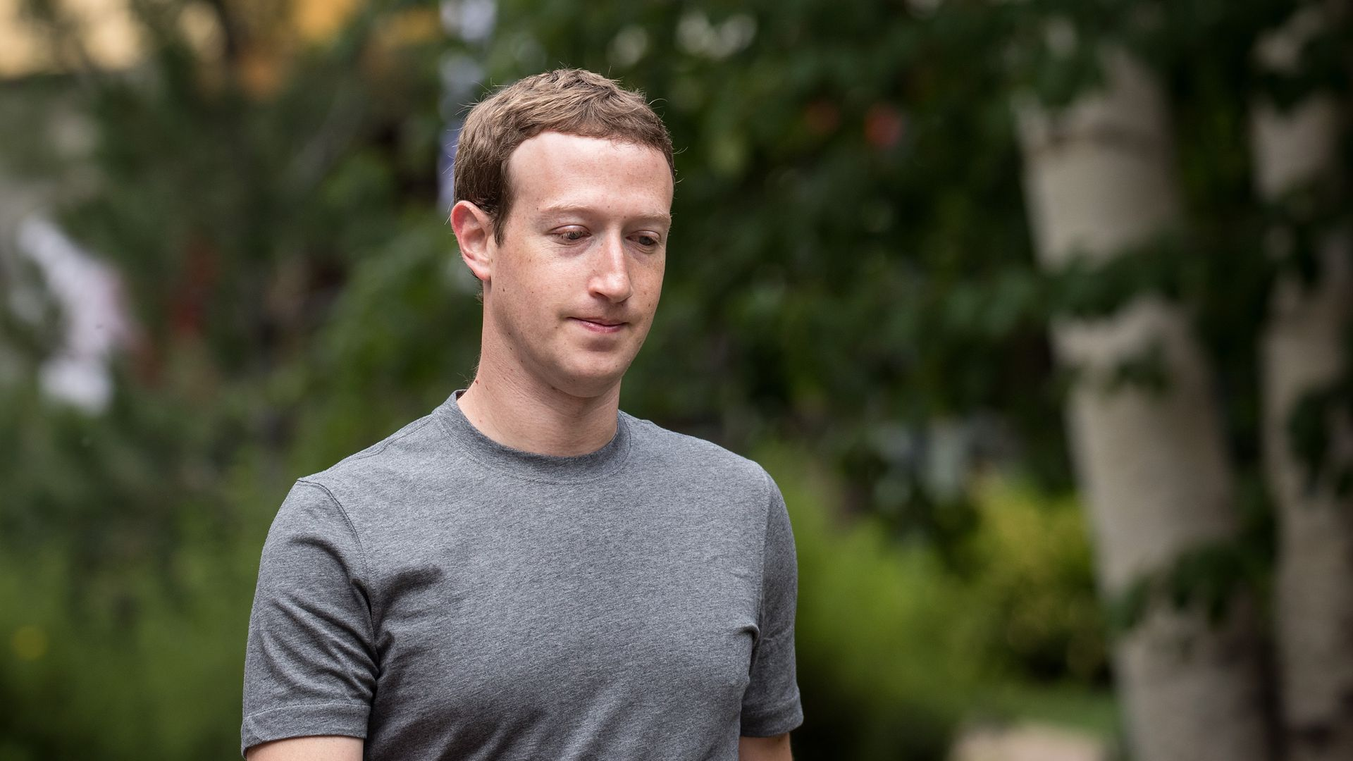 Facebook CEO Mark Zuckerberg walks with trees behind him