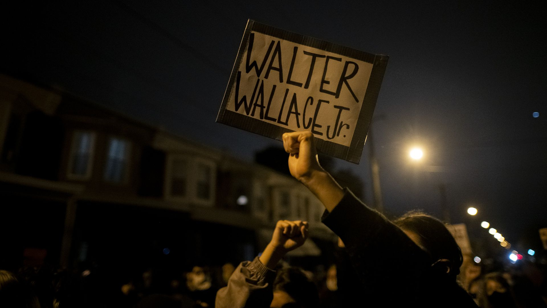 A demonstrator holding placard during a protest near the location where Walter Wallace Jr. was killed by two police officers on Oct. 26, 2020. Photo: Mark Makela/Getty Images