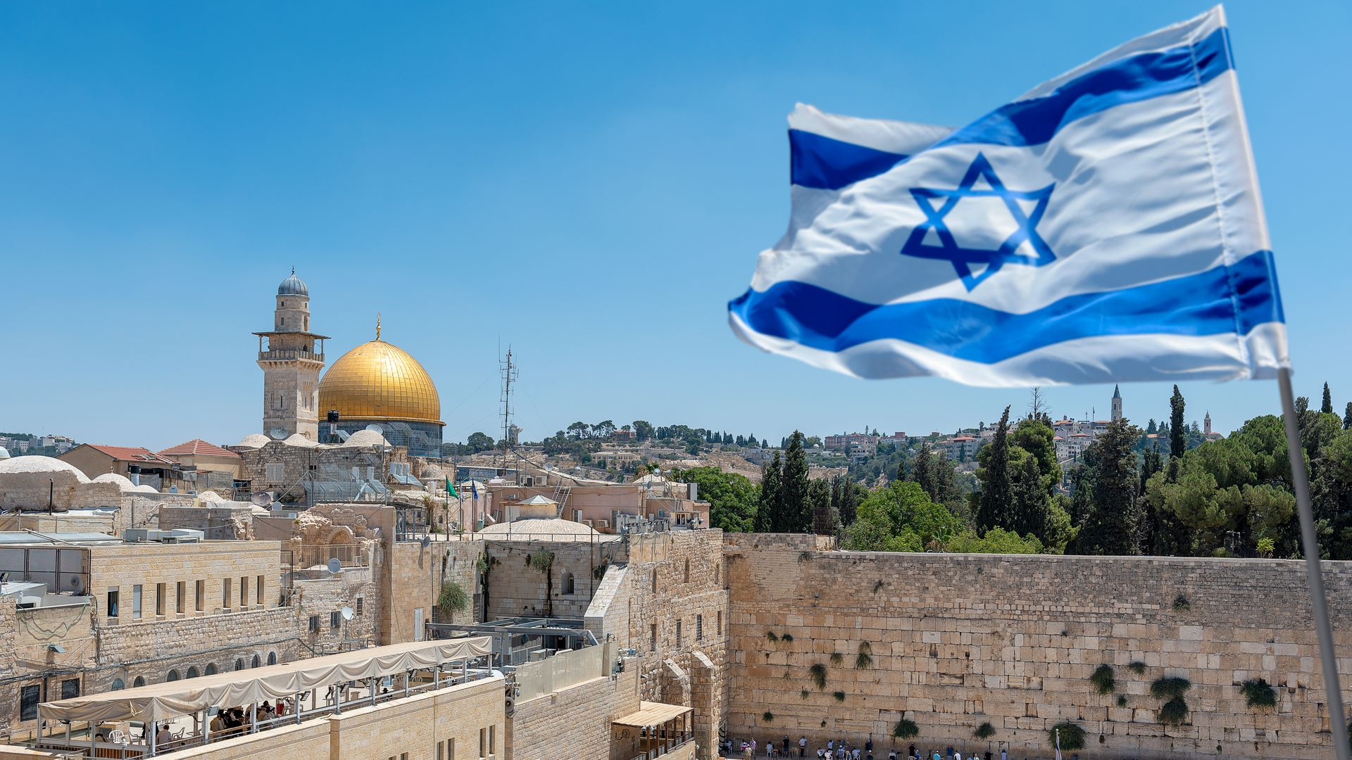 The Wailing Wall and Israeli flag with Al-Aqsa mosque in the background