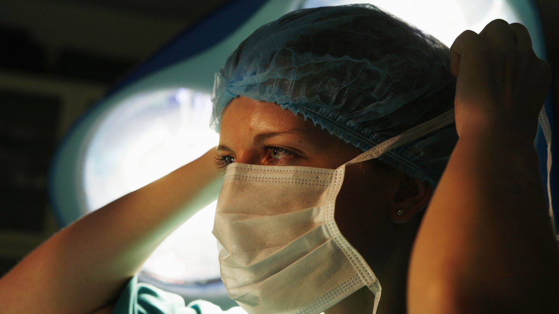 A female surgeon ties her surgical mask around her face.