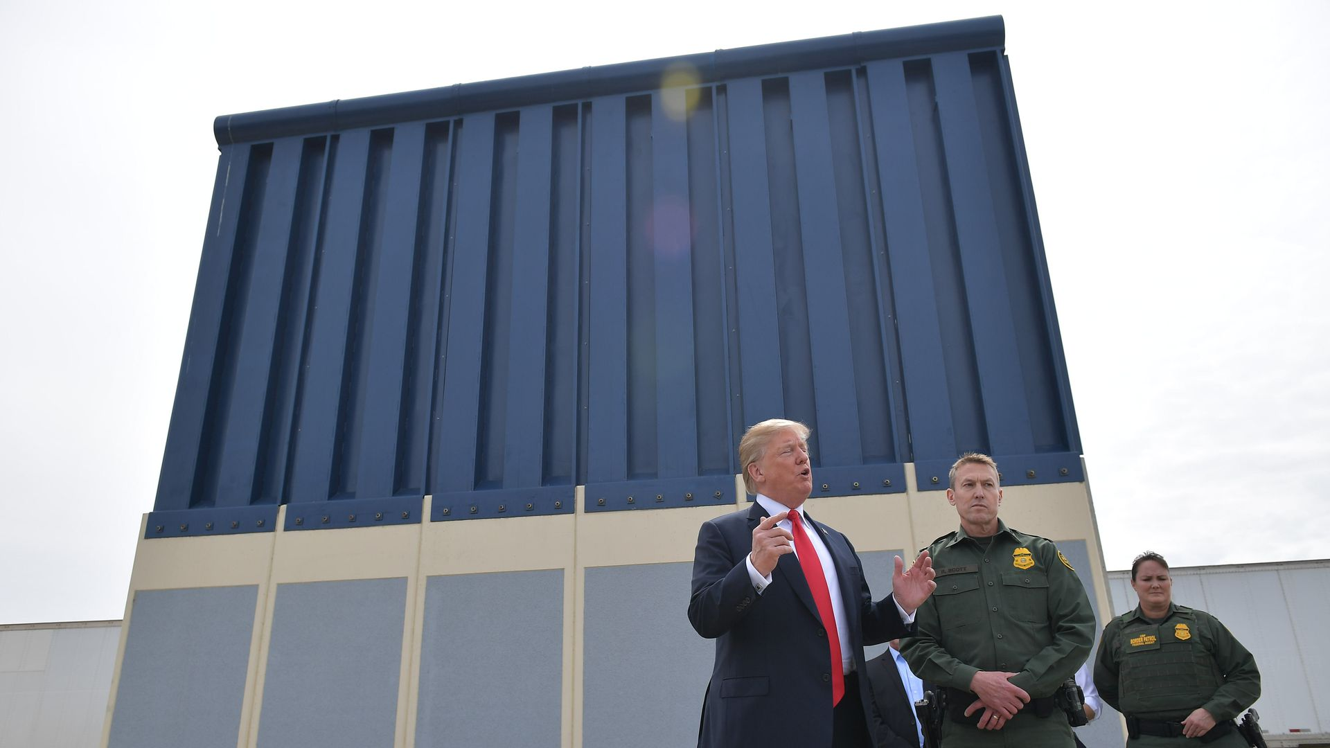 Trump stands and talks in front of a blue prototype of his border wall, next to two border patrol officials.