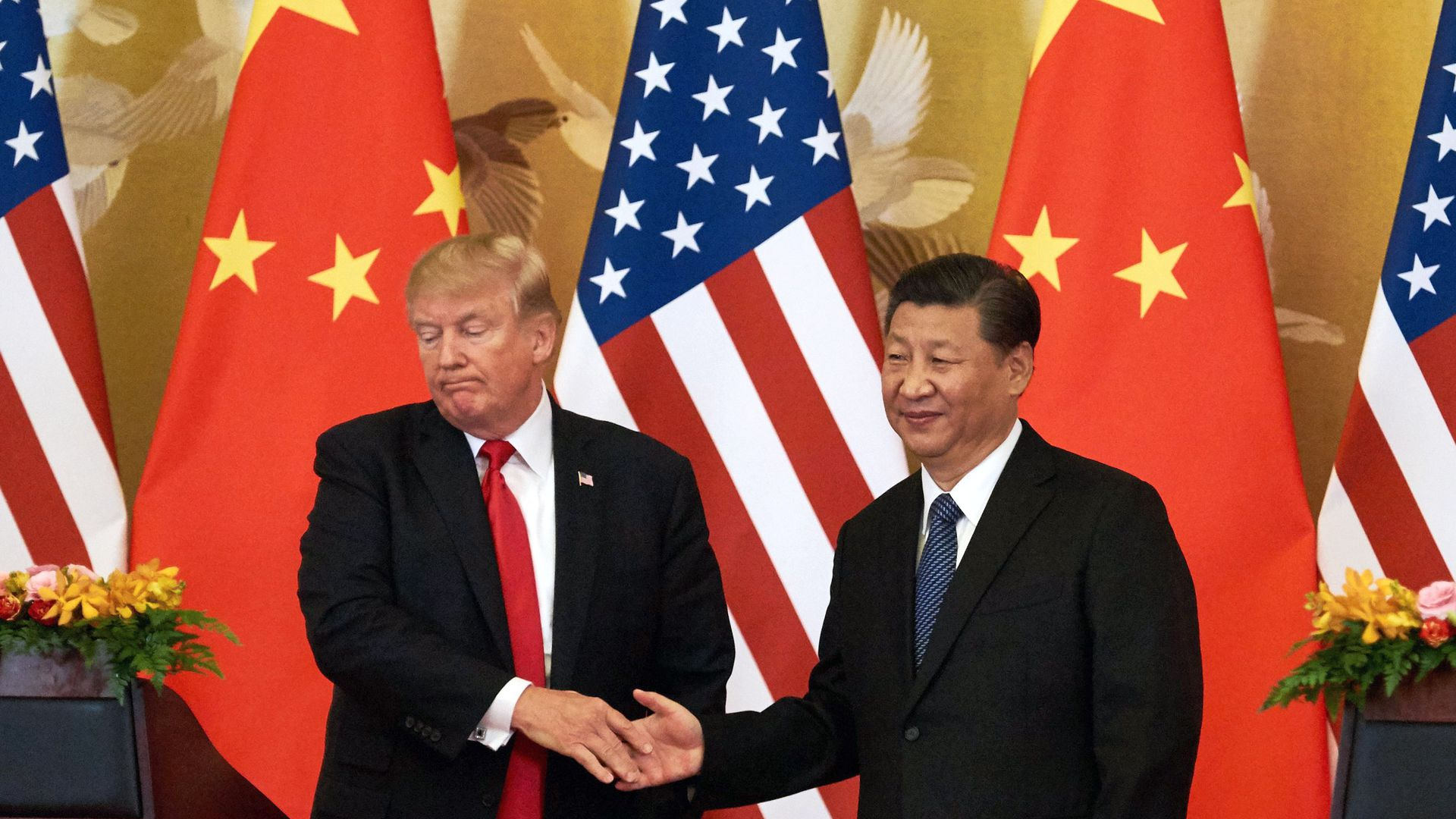 Donald Trump grimaces while shaking hands with Xi Jinping before American and Chinese flags.