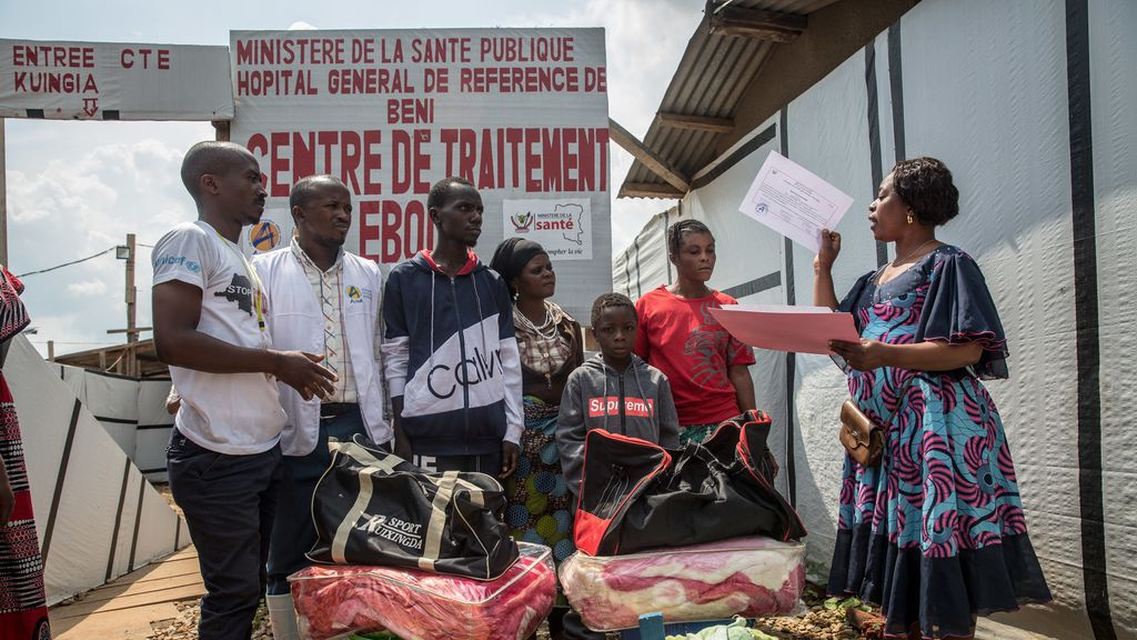 Photo shows a boy receiving a certificate confirming he is Ebola-free, outside an Ebola treatment center in Beni, DRC.