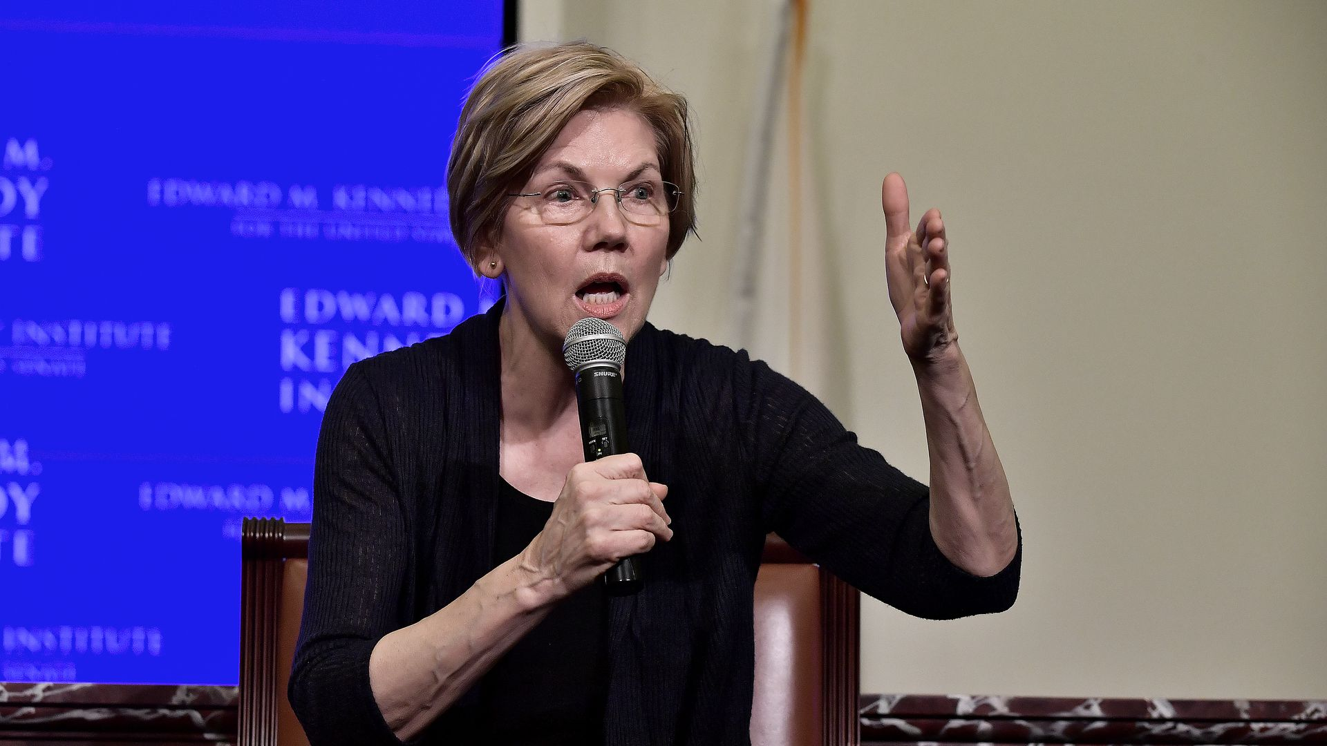 Senator Liz Warren gestures while holding a microphone, wearing black, before a blue and white background.