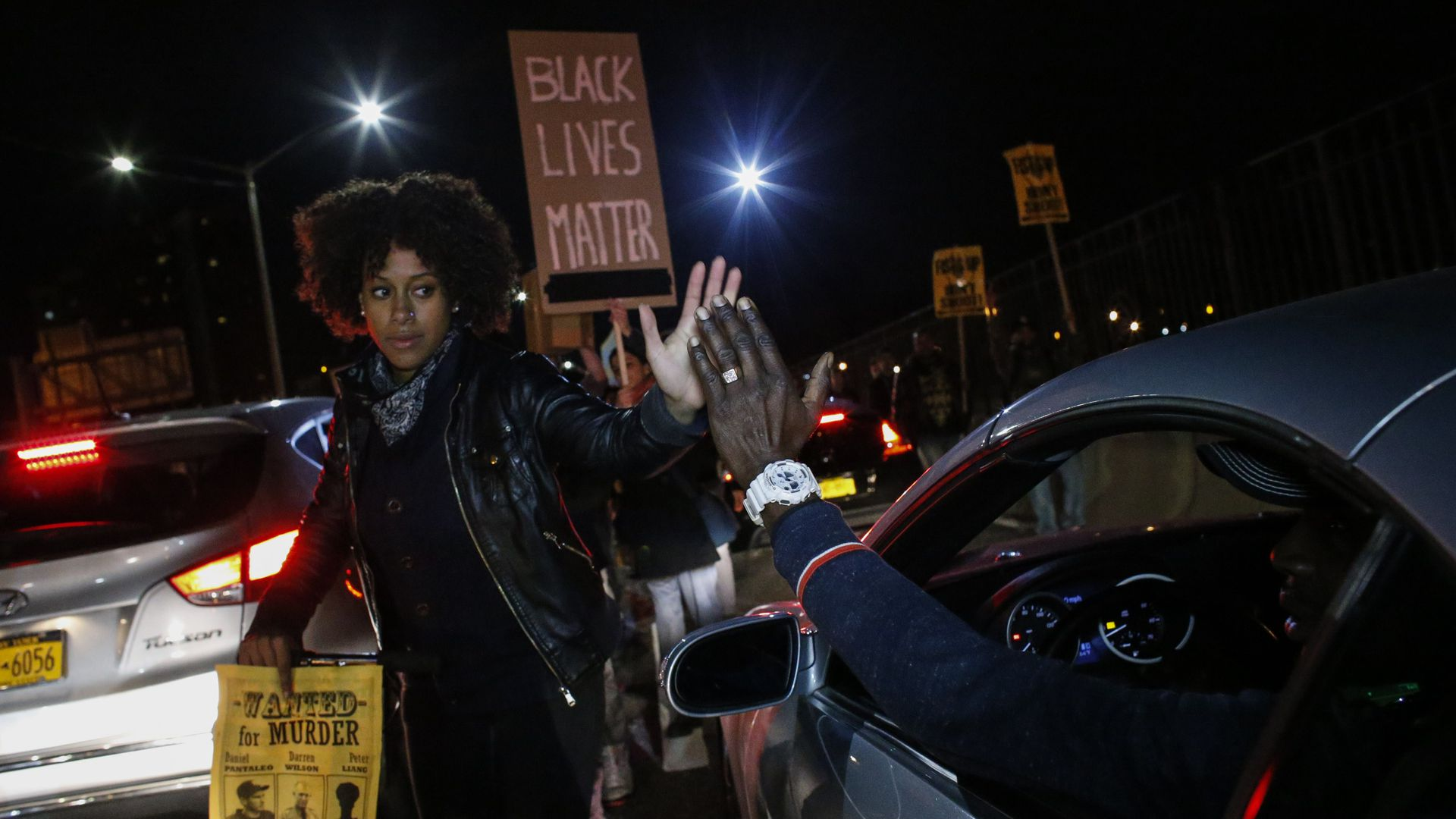 A driver shakes hands with a demonstrator during a protest march in New York City after a grand jury declined to prosecute a white police officer for the killing Michael Brown.