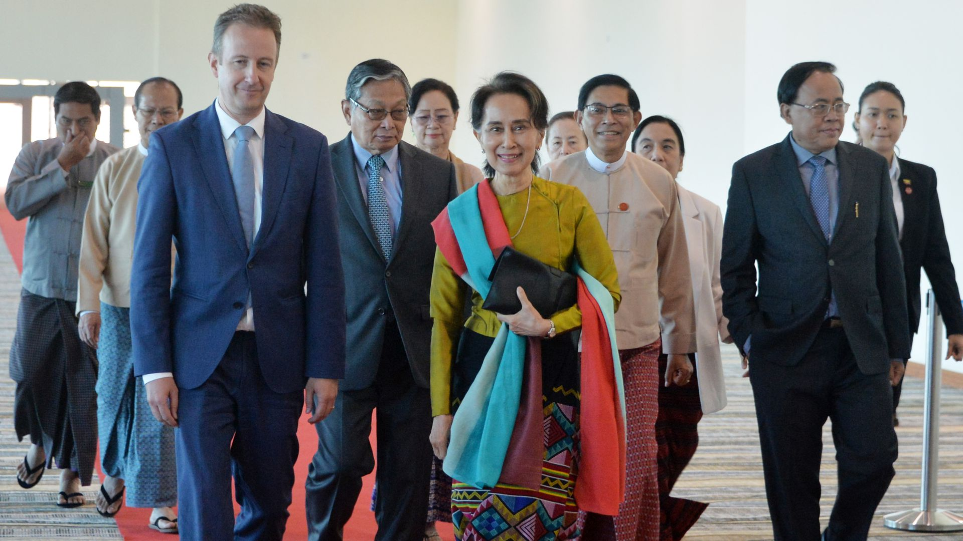 Aung San Suu Kyi, flanked by officials, leaving the nation's capital, Naypyidaw