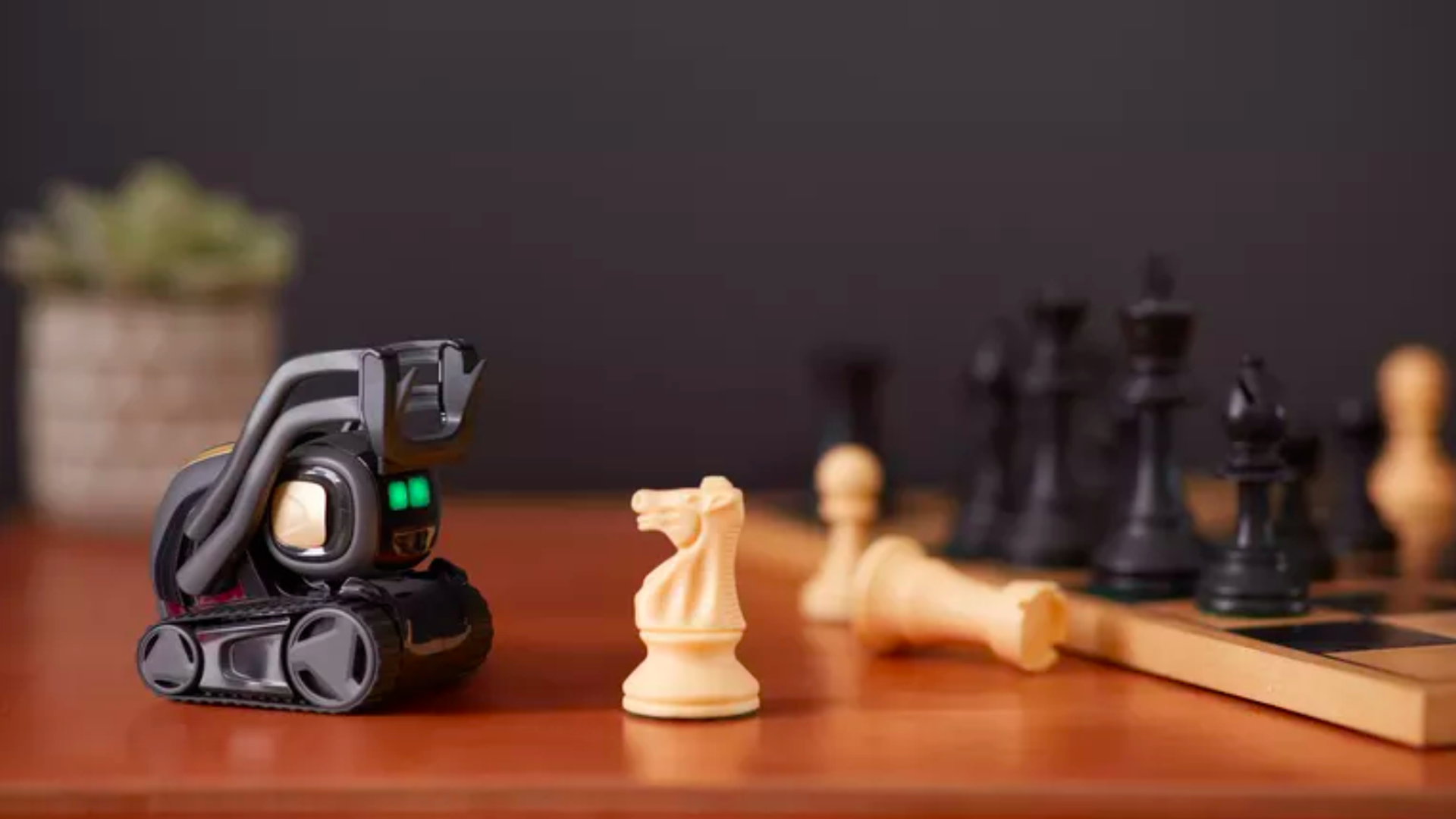 In this image, an Anki robot faces a chess board and a rook stands in front of it.