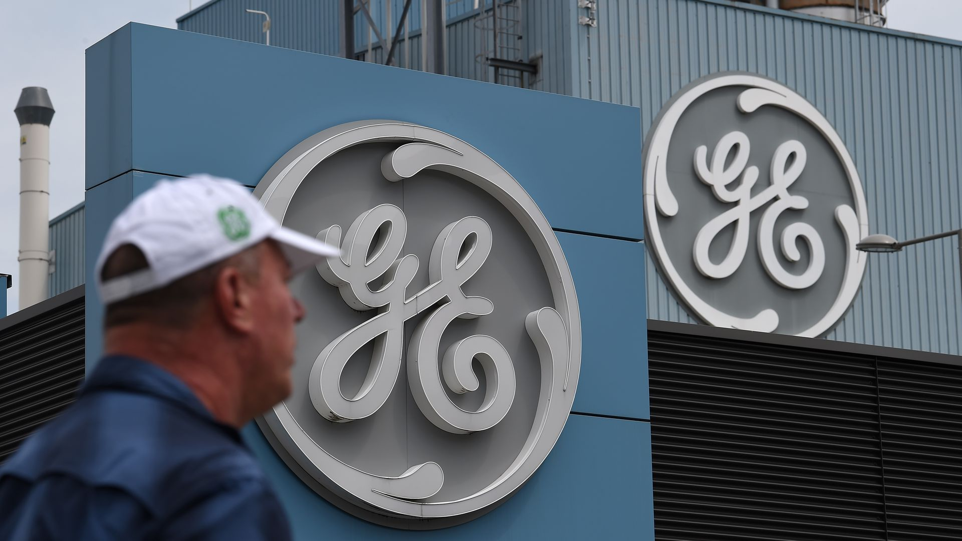 In this image, a man wearing a baseball cap walks in front of a building with a giant General Electric logo.